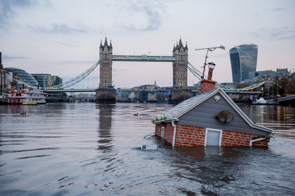 Environmental protest group Extinction Rebellion floats a replica of a British house in front of Tower Bridge on the river Thames in an action entitled 'Our House Is Flooding' on November 10, 2019 in London, England.