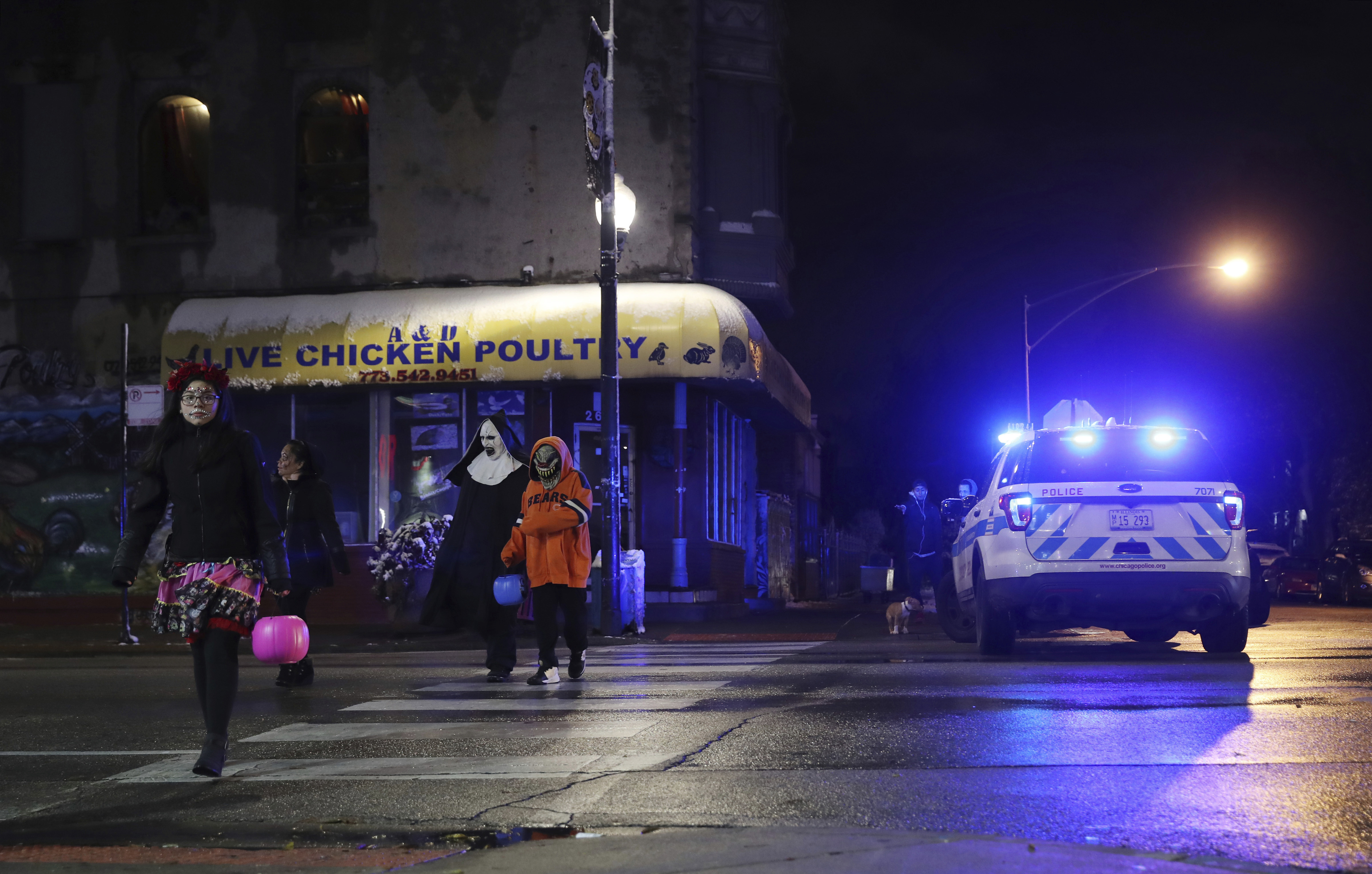 Trick-or-treaters walk past a crime scene in the 3700 block of West 26th Street, where a 7-year-old girl was shot while trick-or-treating Thursday, Oct. 31, 2019, in Chicago. A 7-year-old girl out trick-or-treating in a bumblebee outfit was critically injured Thursday night during a shooting on Chicago's West Side.