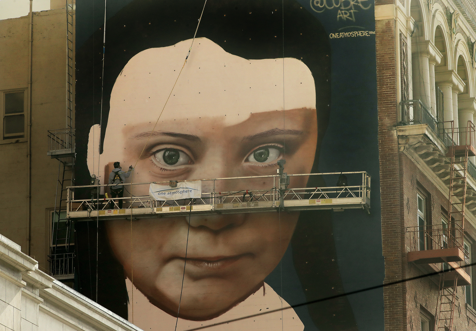 Andres Petreselli paints a mural on the side of a building depicting Swedish teen climate activist Greta Thunberg, Friday, Nov. 8, 2019, in San Francisco.