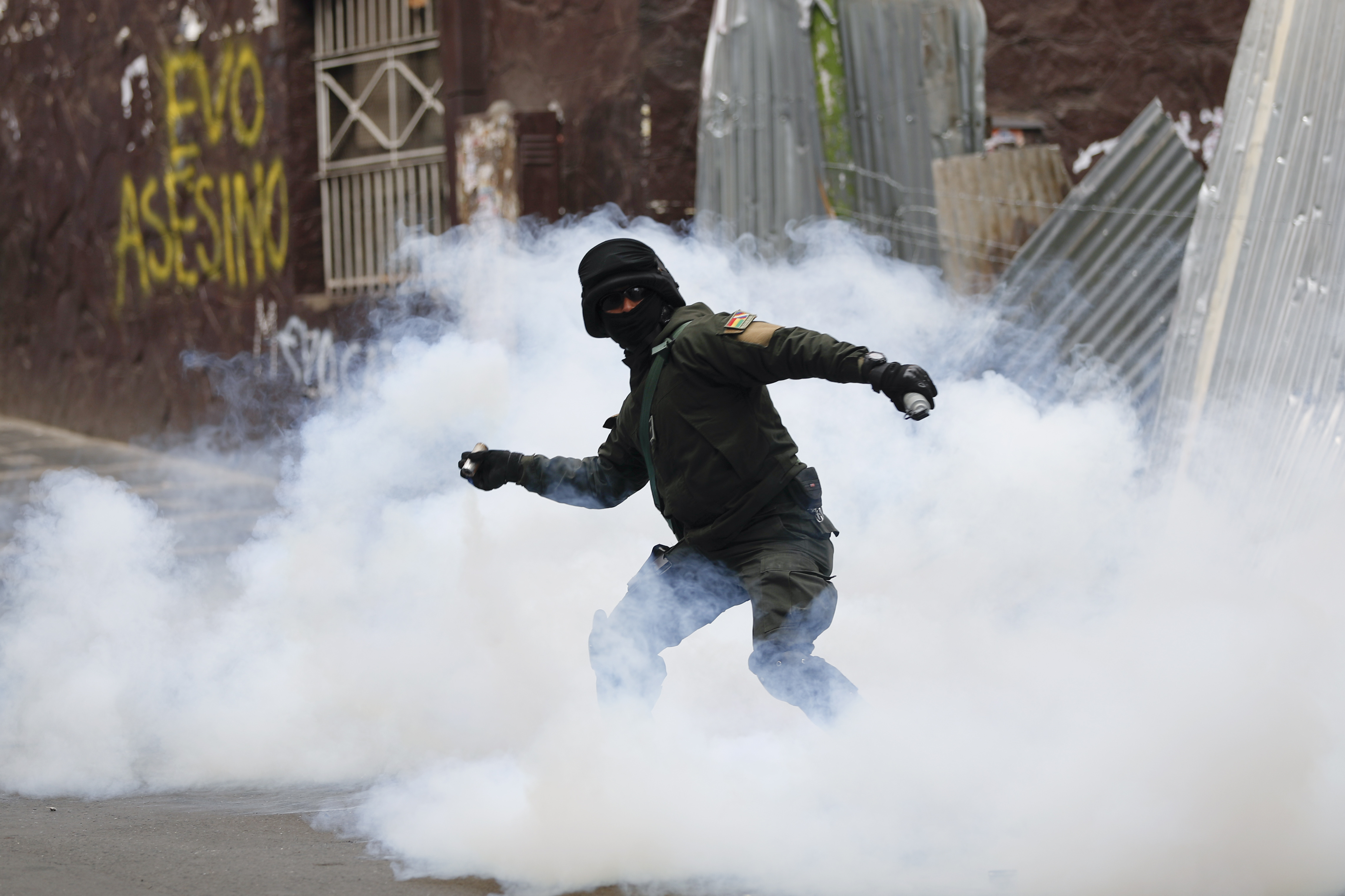 A Bolivian police officer hurls tear gas at backers of former President Evo Morales during clashes, in La Paz, Bolivia, Wednesday, Nov. 13, 2019.