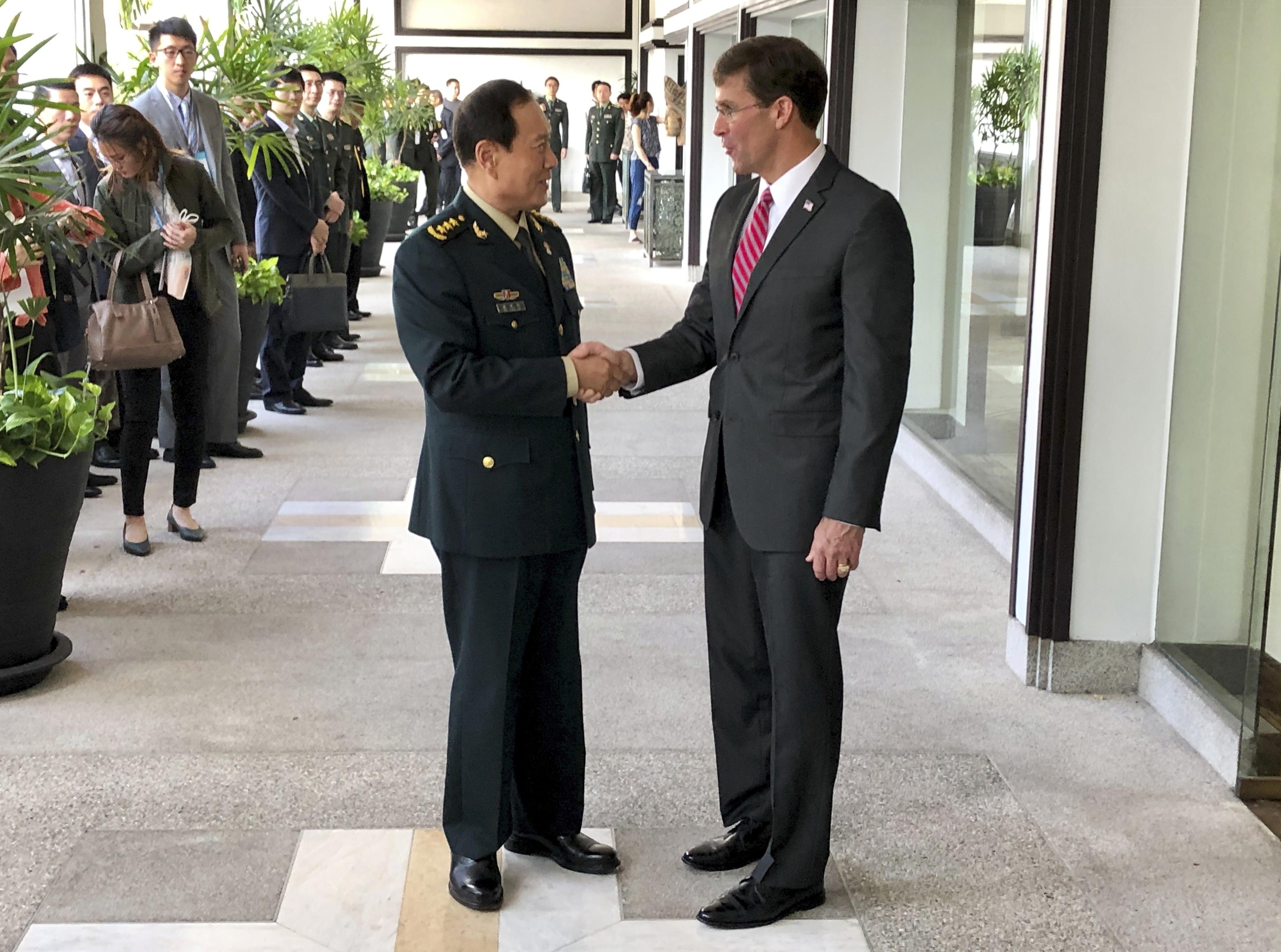 Chinese Defense Minister Wei Fenghe, left, greets U.S. Defense Secretary Mark Esper in Bangkok, Thailand, Monday, Nov. 18, 2019.