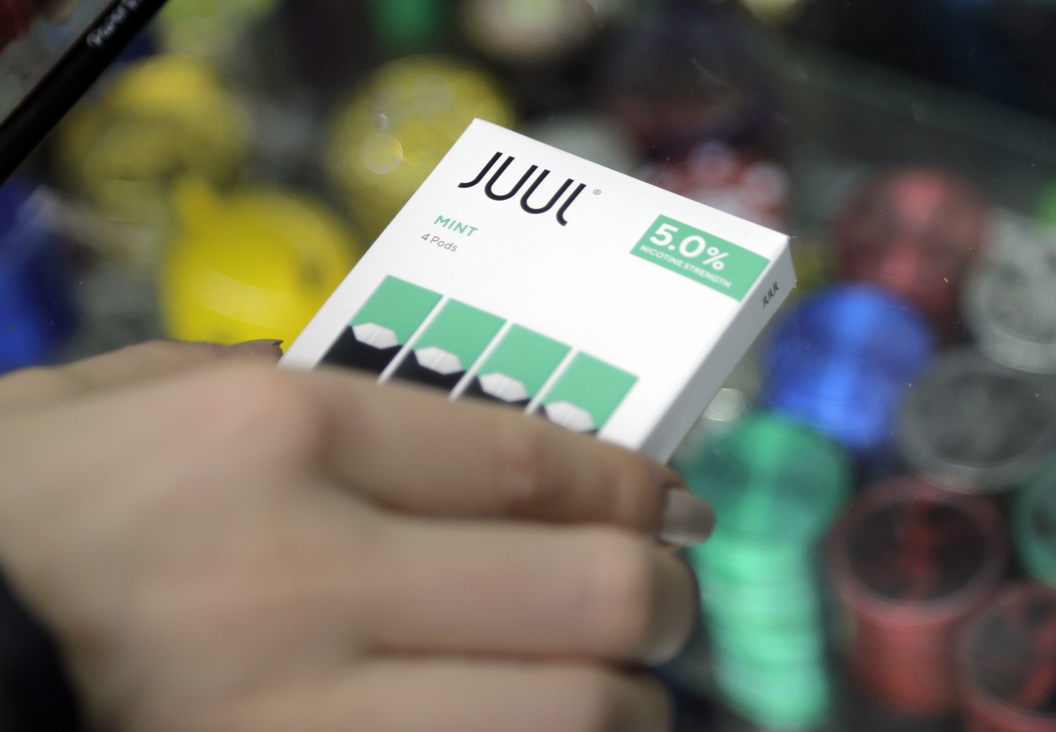 In this Dec. 20, 2018, file photo a woman buys refills for her Juul at a smoke shop in New York.