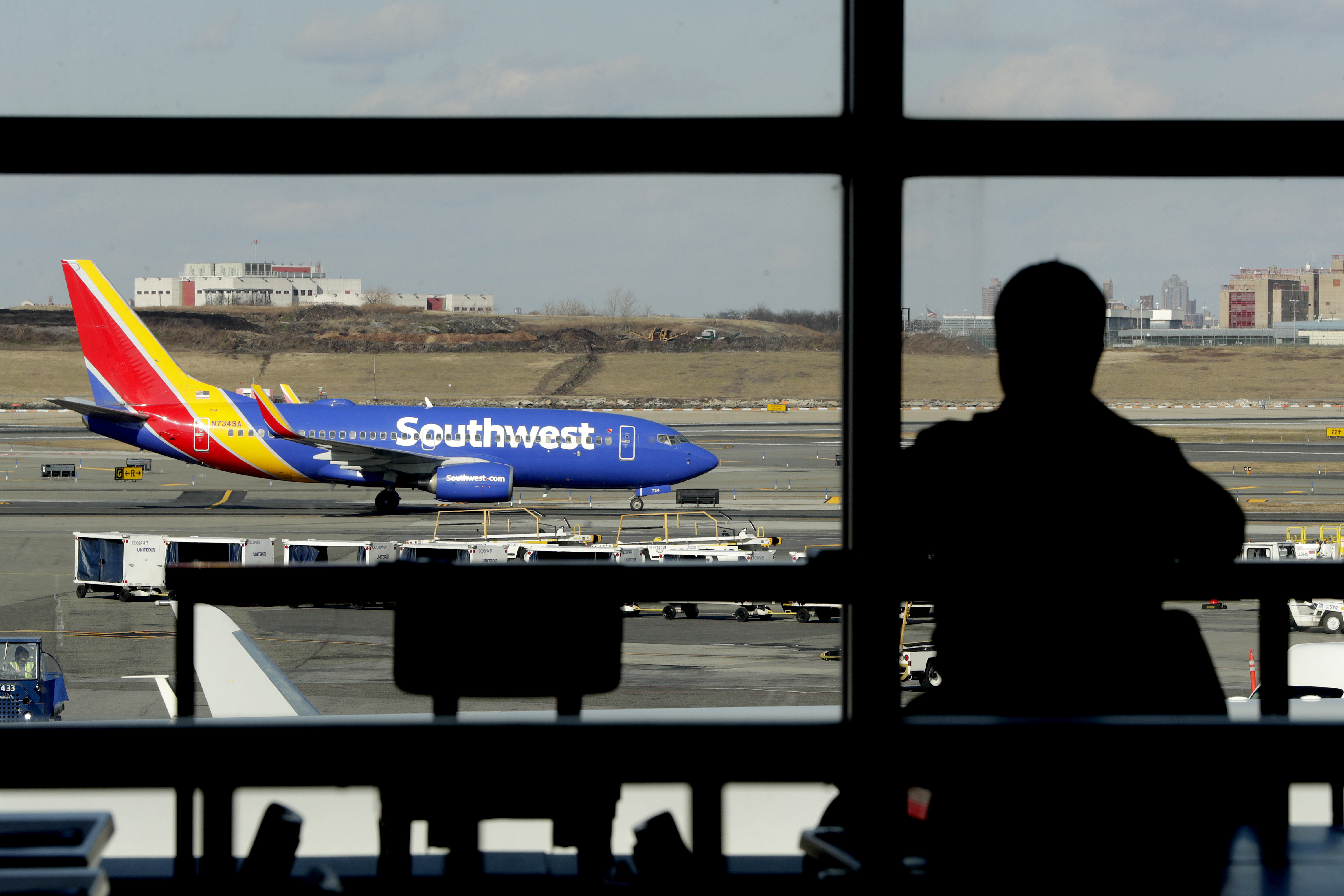 A Southwest Airlines jet moves on the runway as a person eats at a terminal restaurant at LaGuardia Airport in New York, on Jan 25, 2019.