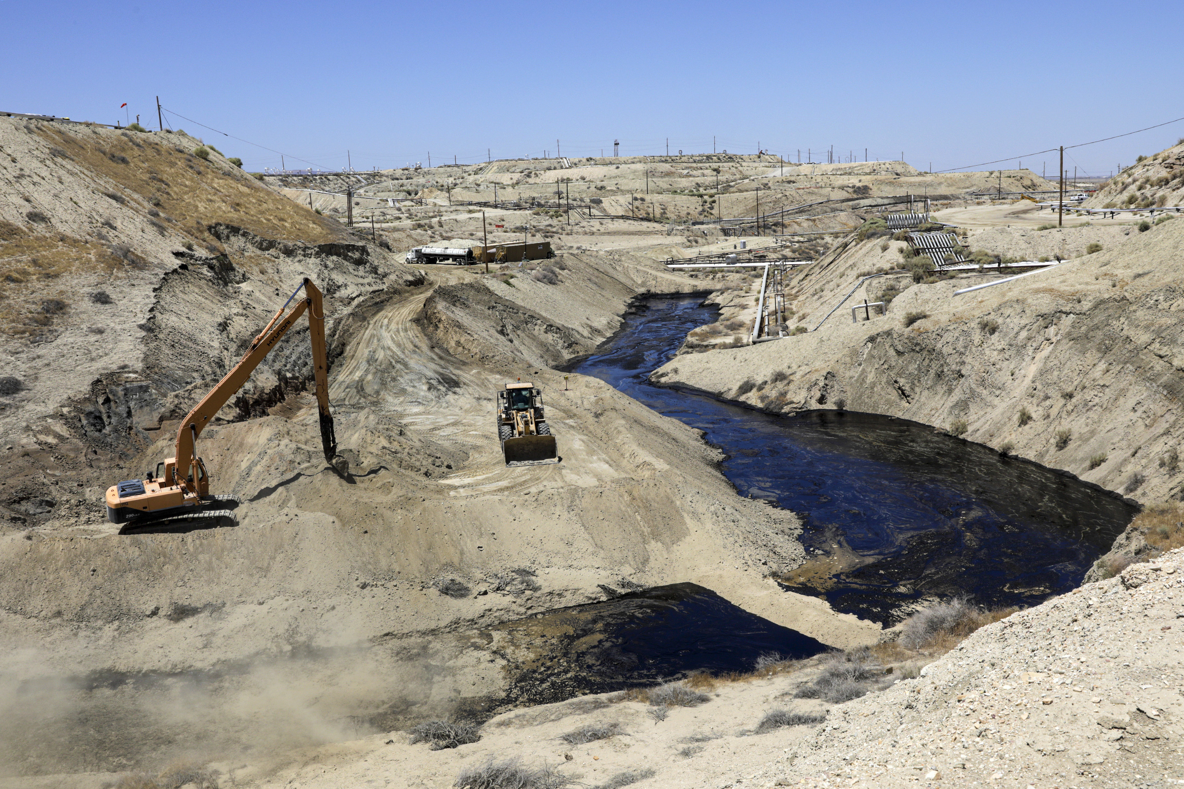 A crew works on seepage of 800,000 gallons of oil and brine water oil from an abandoned well in Chevron Corp's Cymric Oil Field in McKittrick, Calif., on July 24, 2019.