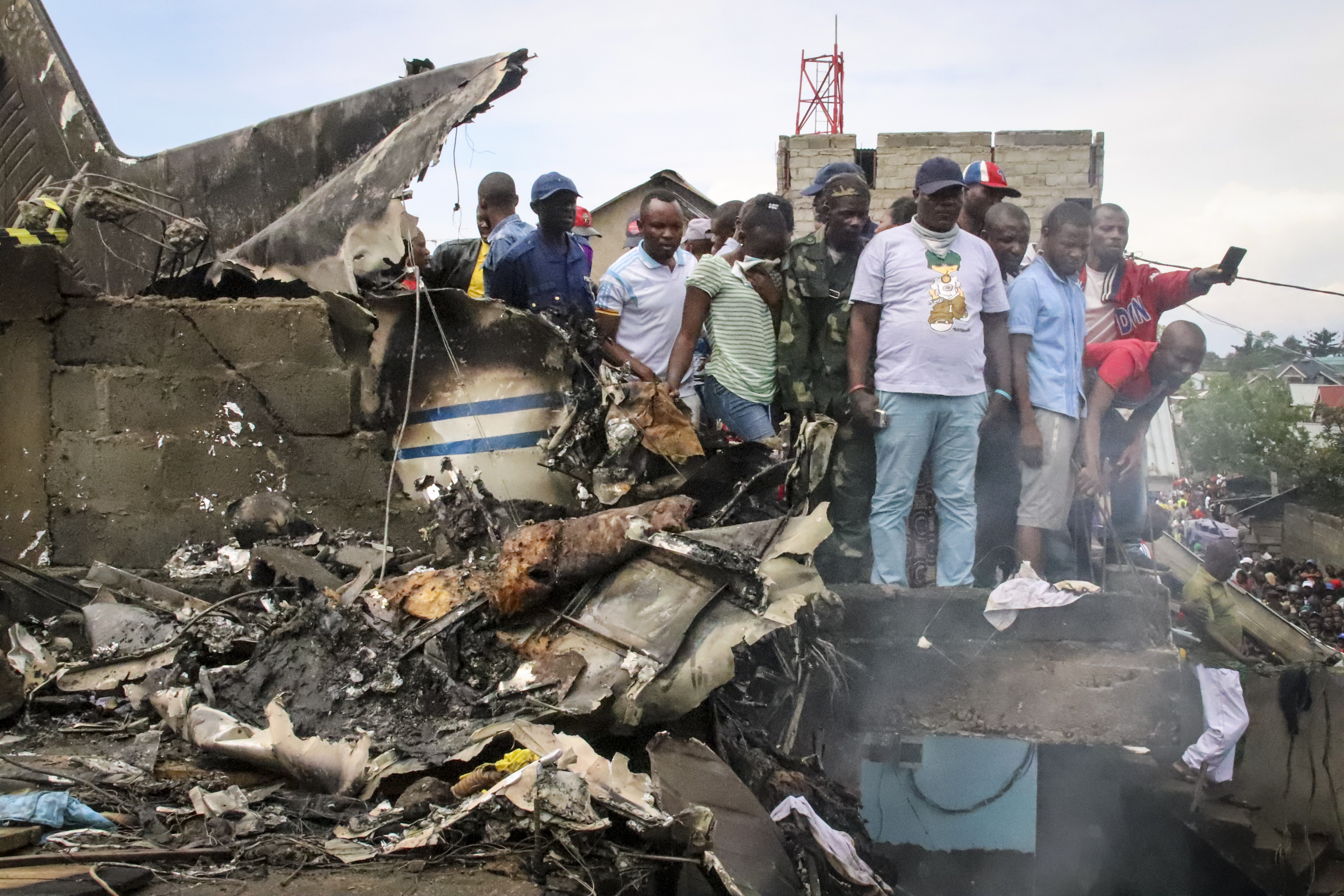 Rescuers and onlookers gather amidst the debris of an aircraft operated by private carrier Busy Bee which crashed in Goma, Congo Sunday, Nov. 24, 2019.