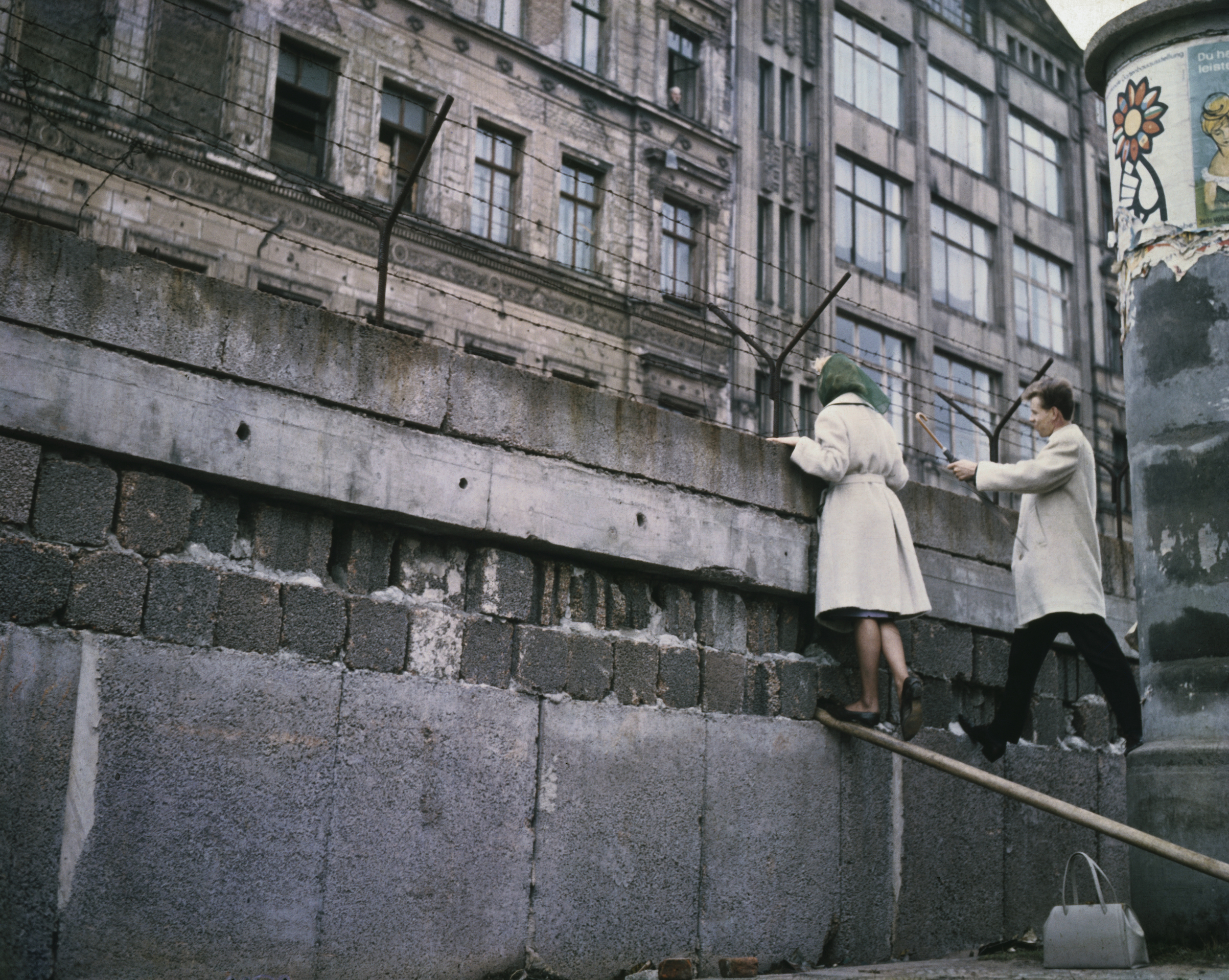 An undated photo of a West Berlin couple talking to relatives in an East Berlin apartment house (see upper window open) over the Berlin Wall.