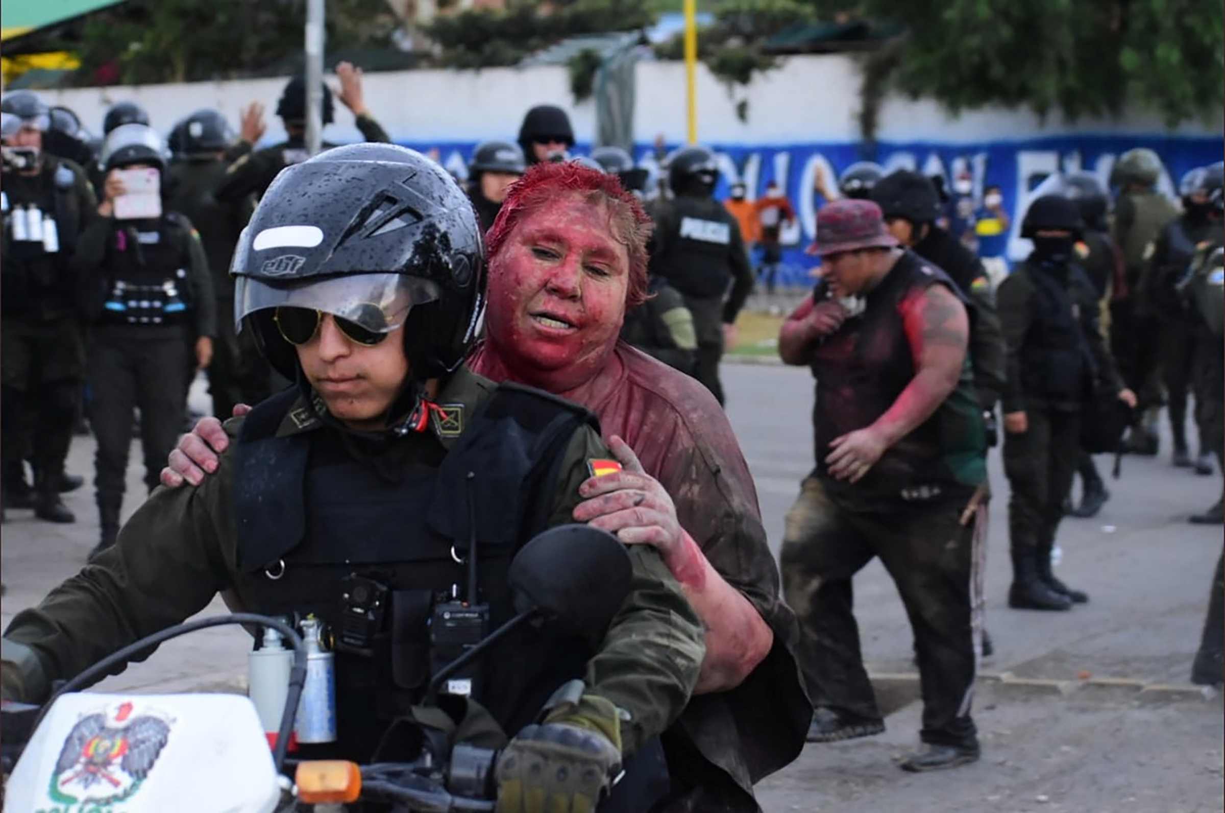 Police rescue Vinto mayor Patricia Arce Guzman on a motorcycle after people threw paint and dirt on her following a fire in Vinto's Town Hall, in Quillacollo, Bolivia, on Nov. 6, 2019.