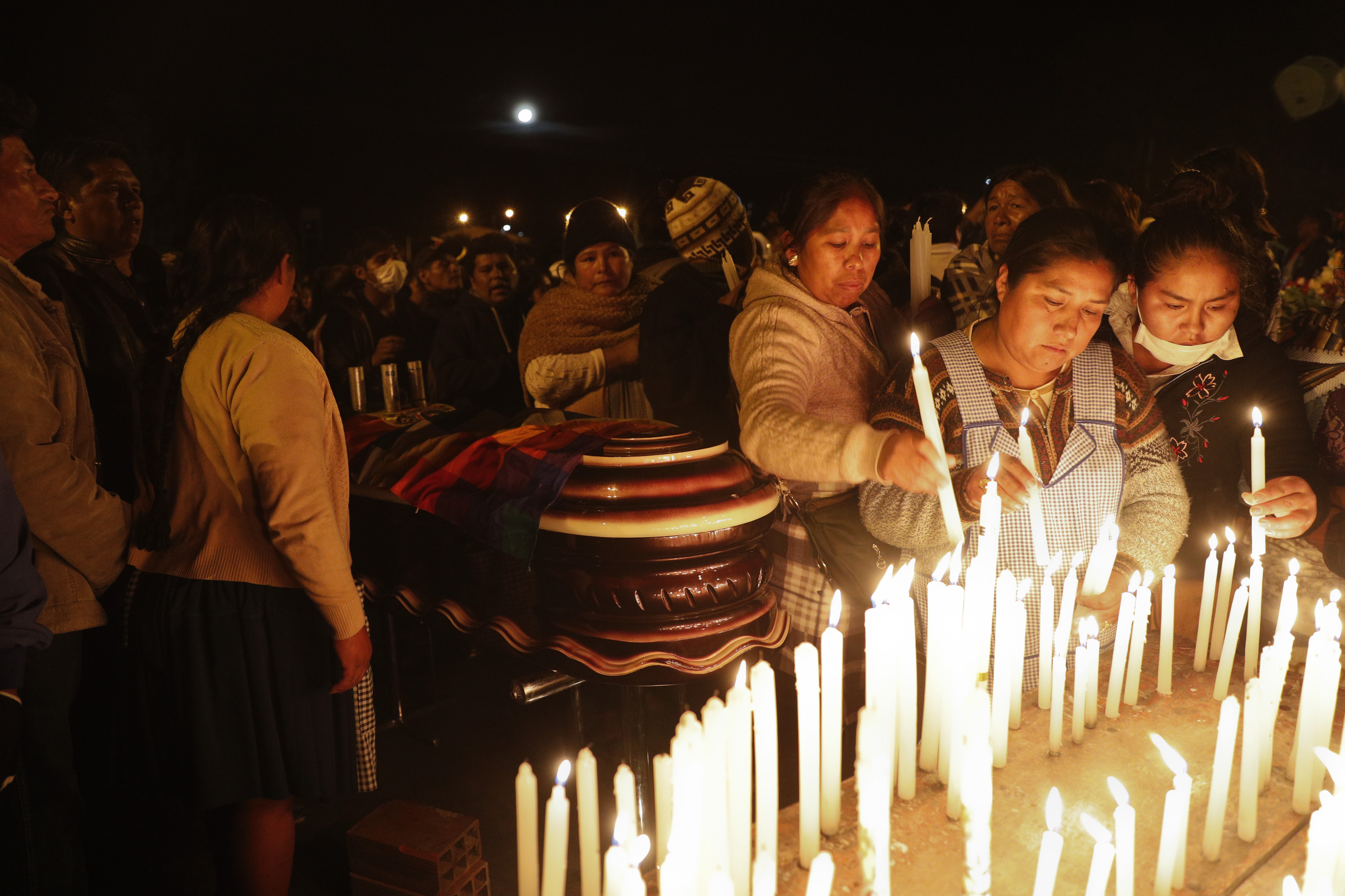 Mourners light candles around coffins of backers of former President Evo Morales that died during clashes with security forces in Sacaba, Bolivia, Friday, Nov. 15, 2019.