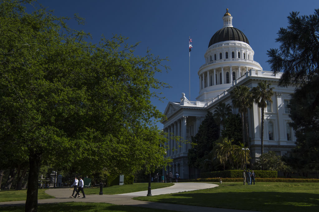 Pedestrians walk past the California State Capitol building in Sacramento.