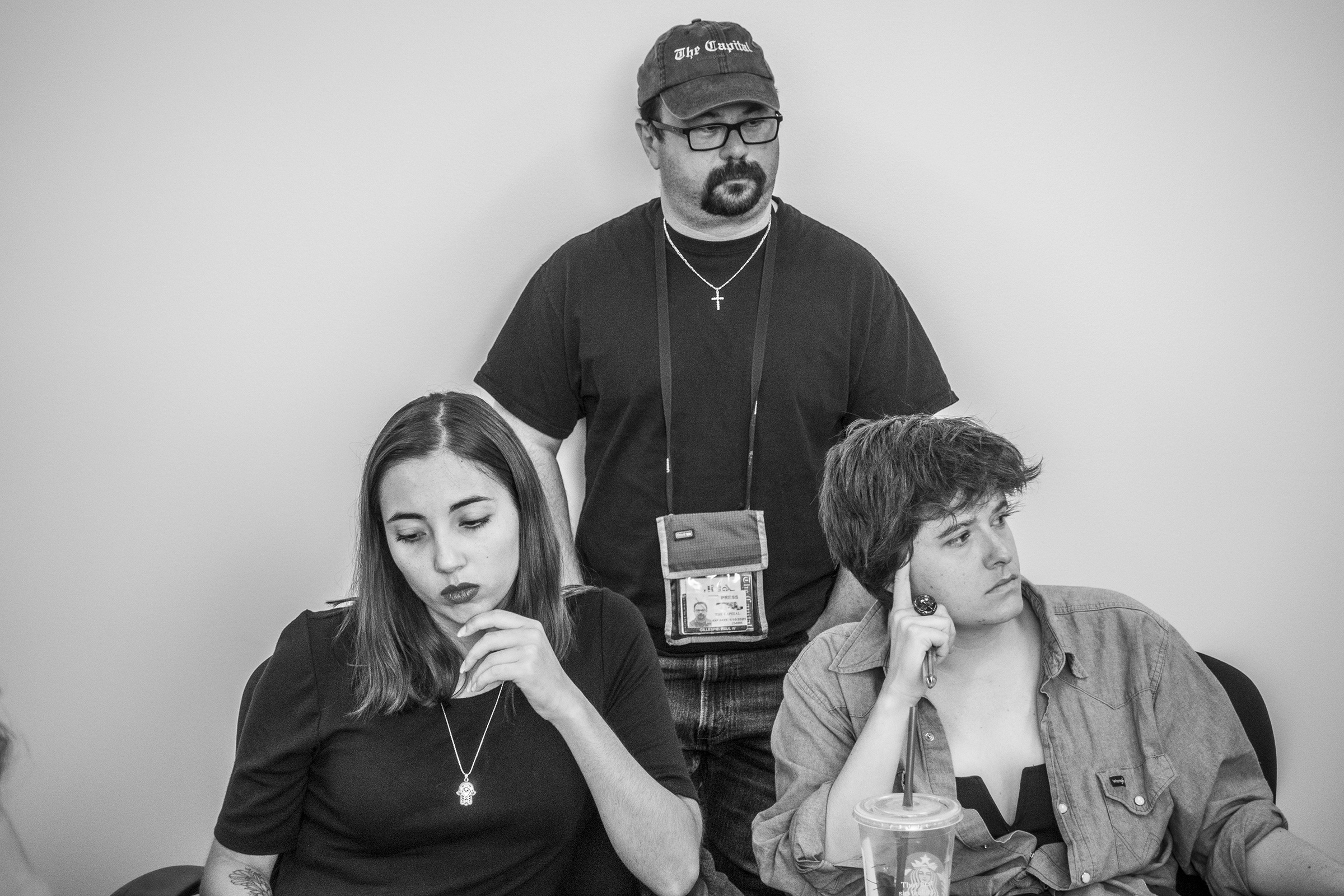 From left: Capital Gazette reporter Selene San Felice, photographer Paul Gillespie, and reporter Rachael Pacella, listen during a meeting at the newspaper, June 5, 2019.