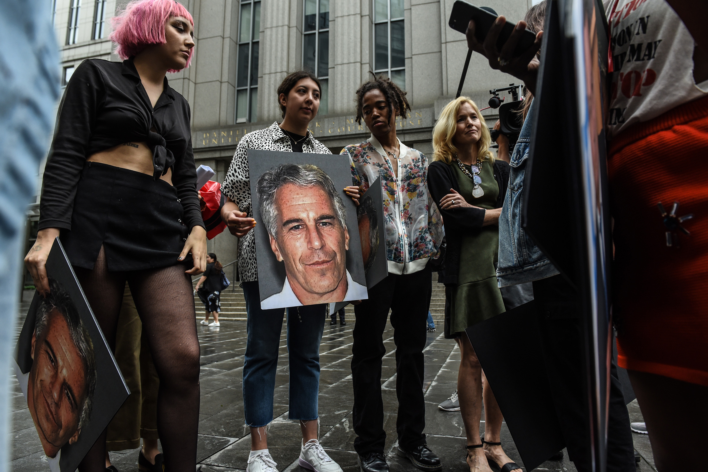 A protest group holds up signs of Jeffrey Epstein in front of the federal courthouse in New York City, July 8, 2019