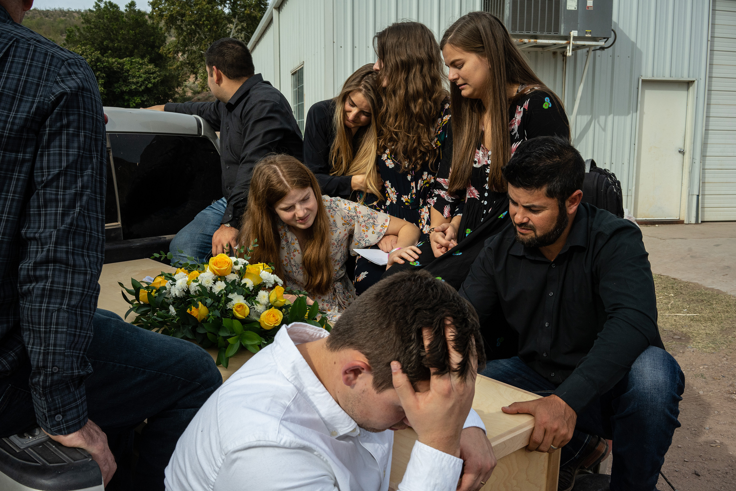 Relatives mourn as a coffin is transported to the graveyard.