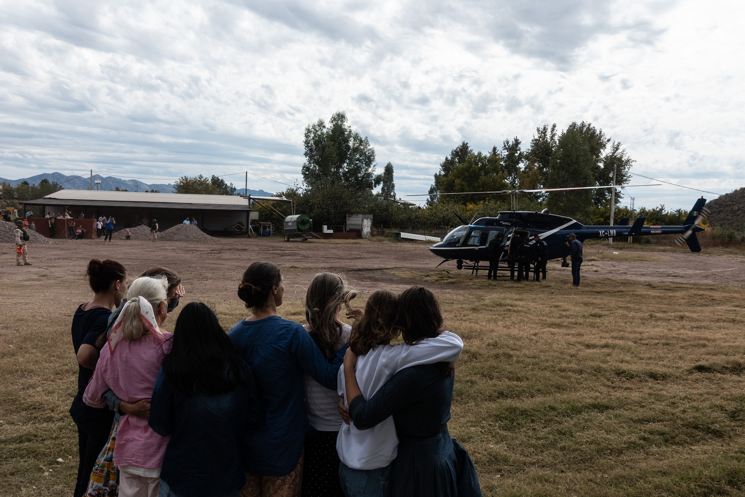 Family members watch a helicopter prepare to leave with the body of Christina Langford Johnson.