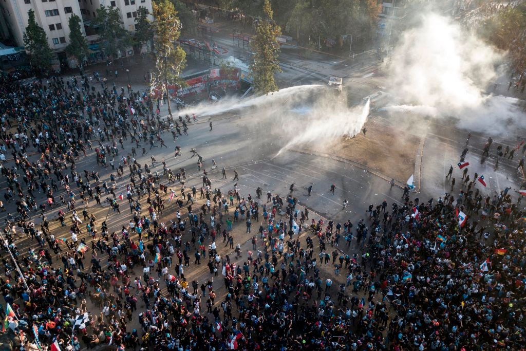 Aerial view of security forces spraying water as people take part in the so-called 'Mourning March' in Santiago on November 01, 2019, to protest against the death of 23 people after more than ten days of civil unrest.