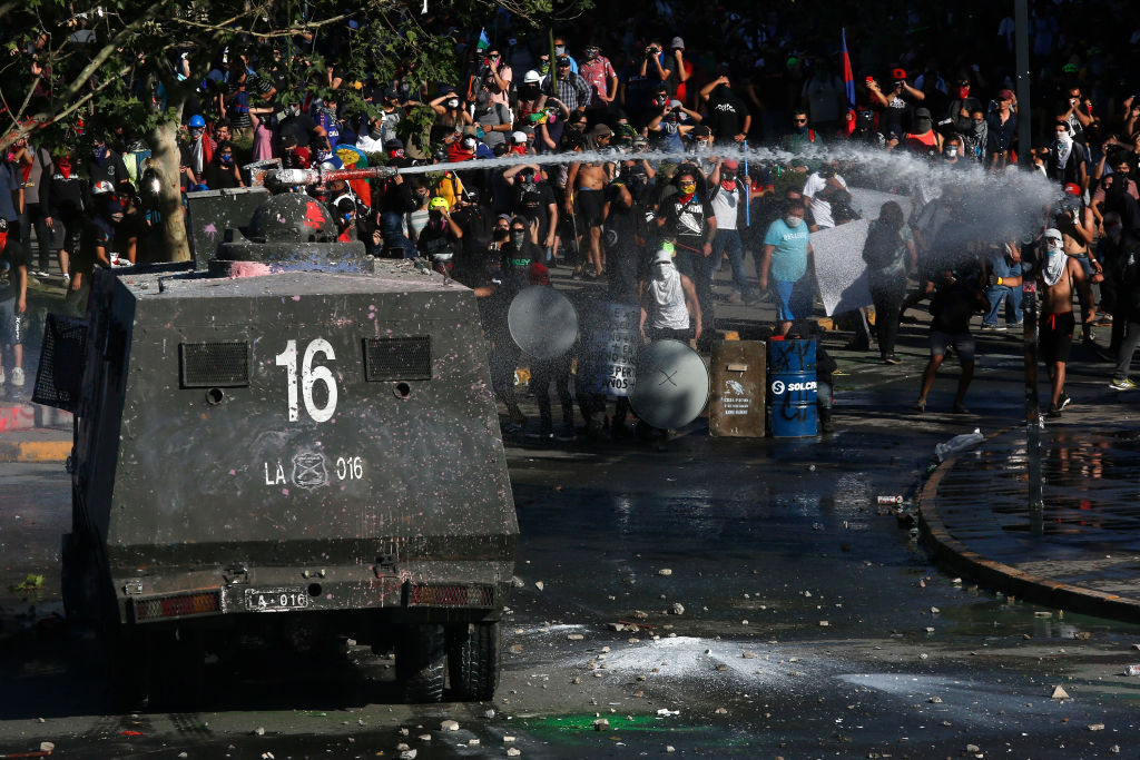 A riot police truck fires water to demonstrators during the ongoing protests against policies of Sebastian Piñera and longstanding inequality on Nov. 15, 2019 in Santiago, Chile. Chilean lawmakers agreed on calling a referendum in April 2020 to replace the current constitution, which was written and approved during General Augusto Pinochet's military dictatorship in 1980. People will be asked if they approve the idea of a new constitution and if current lawmakers should work on the redraft of the document.