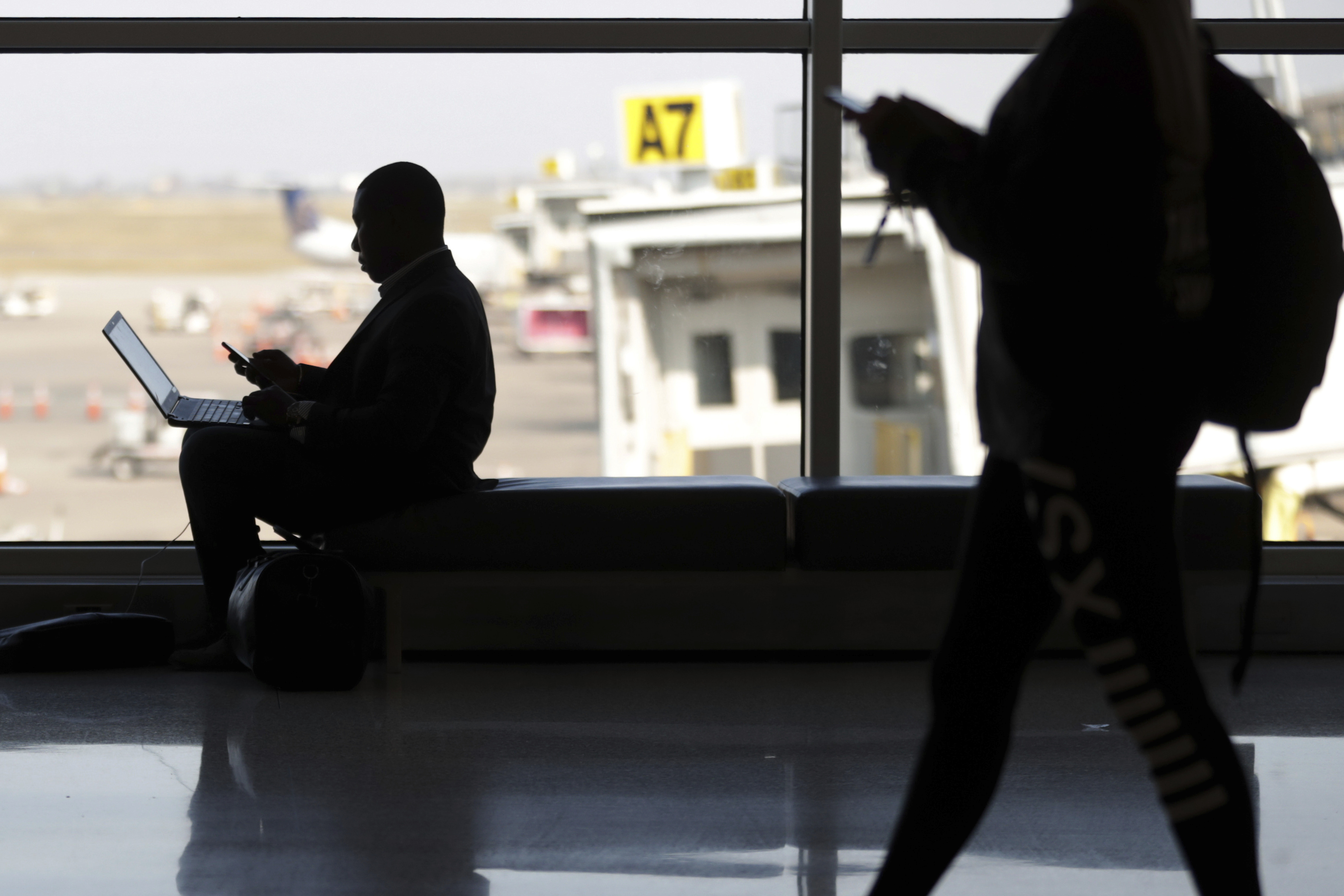 Travelers check their phones at Indianapolis International Airport in Indianapolis on Nov. 21, 2018.