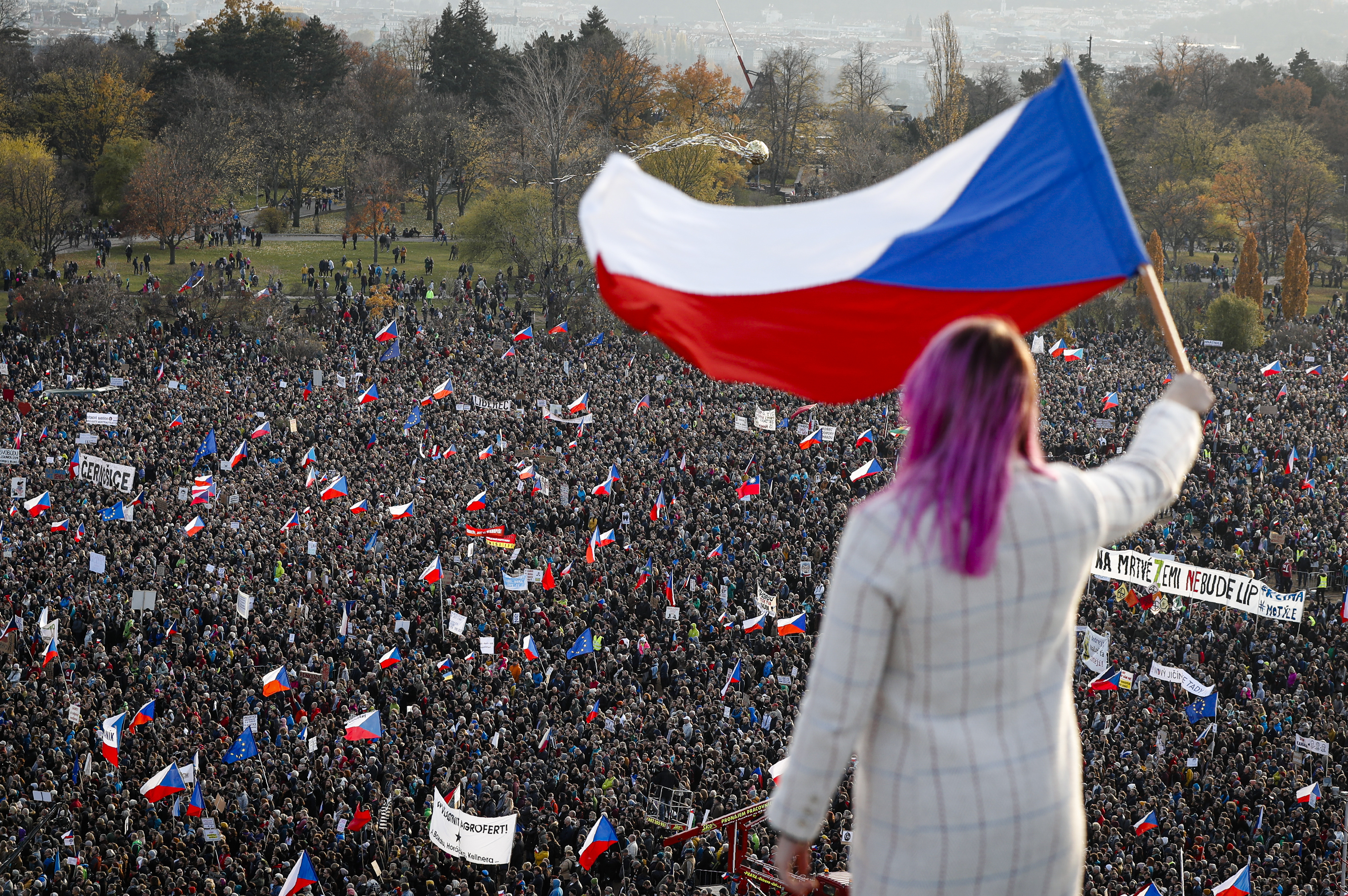 A woman waves a Czech flag from a roof as people take part in a large anti-government protest in Prague, Czech Republic, Saturday, Nov. 16, 2019.