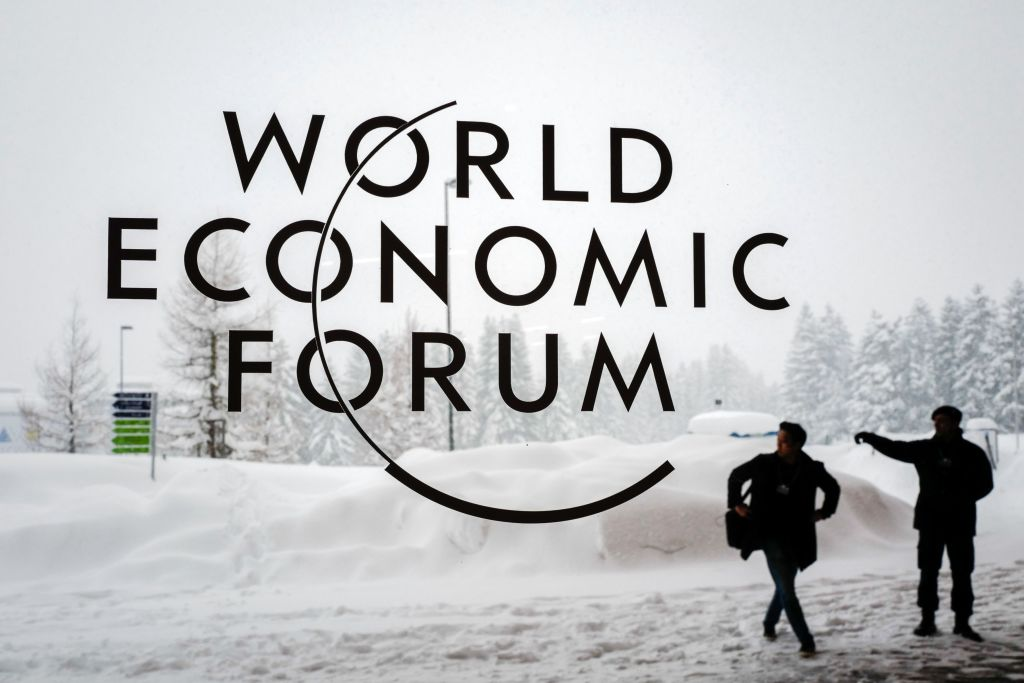 A security guard show the way to a man outside of the Davos Congress Centre under snow ahead of the opening of the World Economic Forum (WEF) 2018 annual meeting, on Jan. 22, 2018 in Davos, eastern Switzerland.