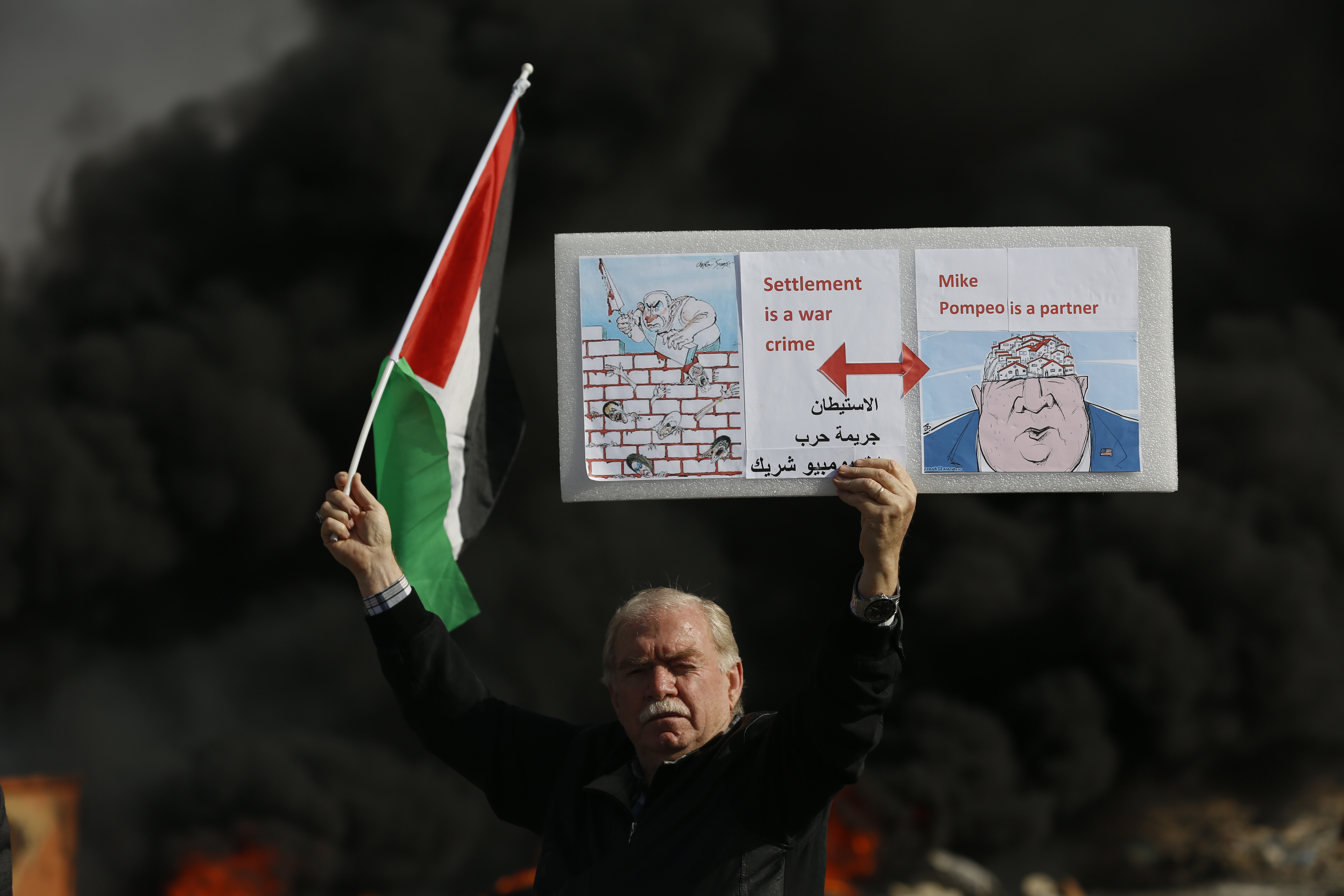 A Palestinian holds a poster depicting Israeli Prime Minister Benjamin Netanyahu, left, and U.S. Secretary of State Mike Pompeo as clashes with Israeli troops broke out during the protest against the U.S. announcement that it no longer believes Israeli settlements violate international law., at checkpoint Beit El near the West Bank city of Ramallah on Nov. 26, 2019.
