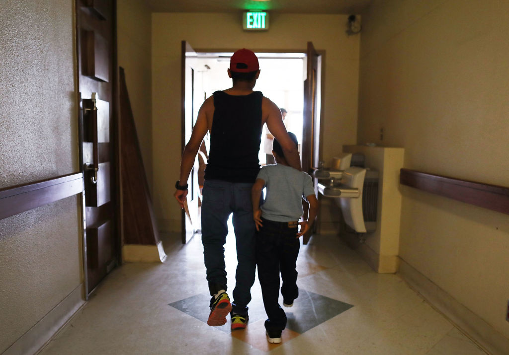 A man, identified only as  Eduardo, walks with his son, Louis, 7, after they were reunited  in El Paso, Texas on July 19, 2018.