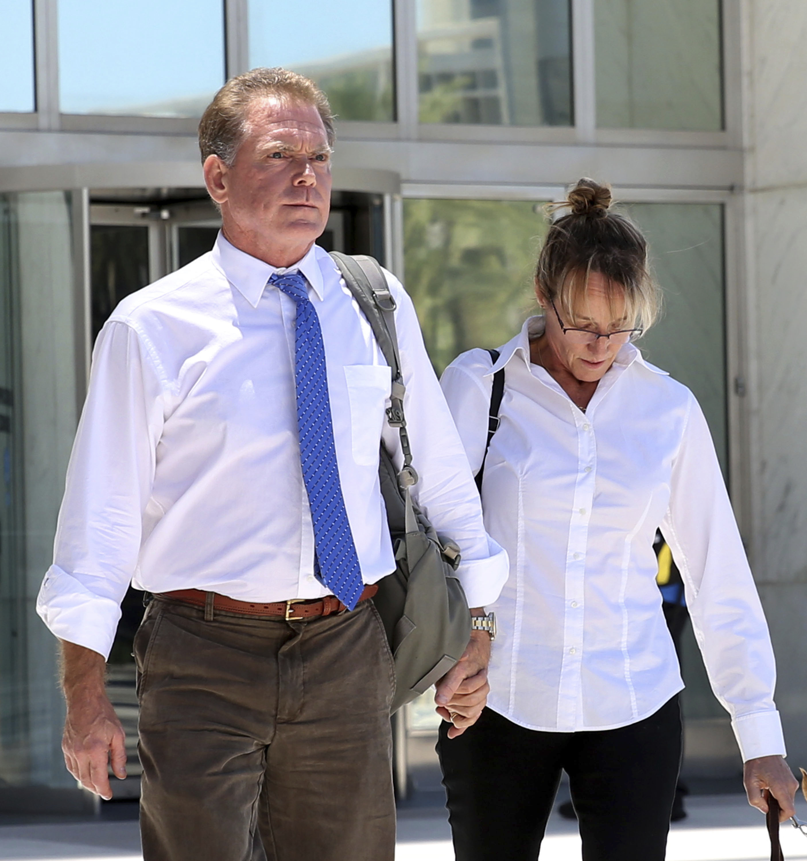 In this July 10, 2019, file photo, Douglas Haig, left, the Arizona man who sold ammunition to the Route 91 Harvest festival gunman, and his wife, Dori, leave the Lloyd George Federal Courthouse in Las Vegas.