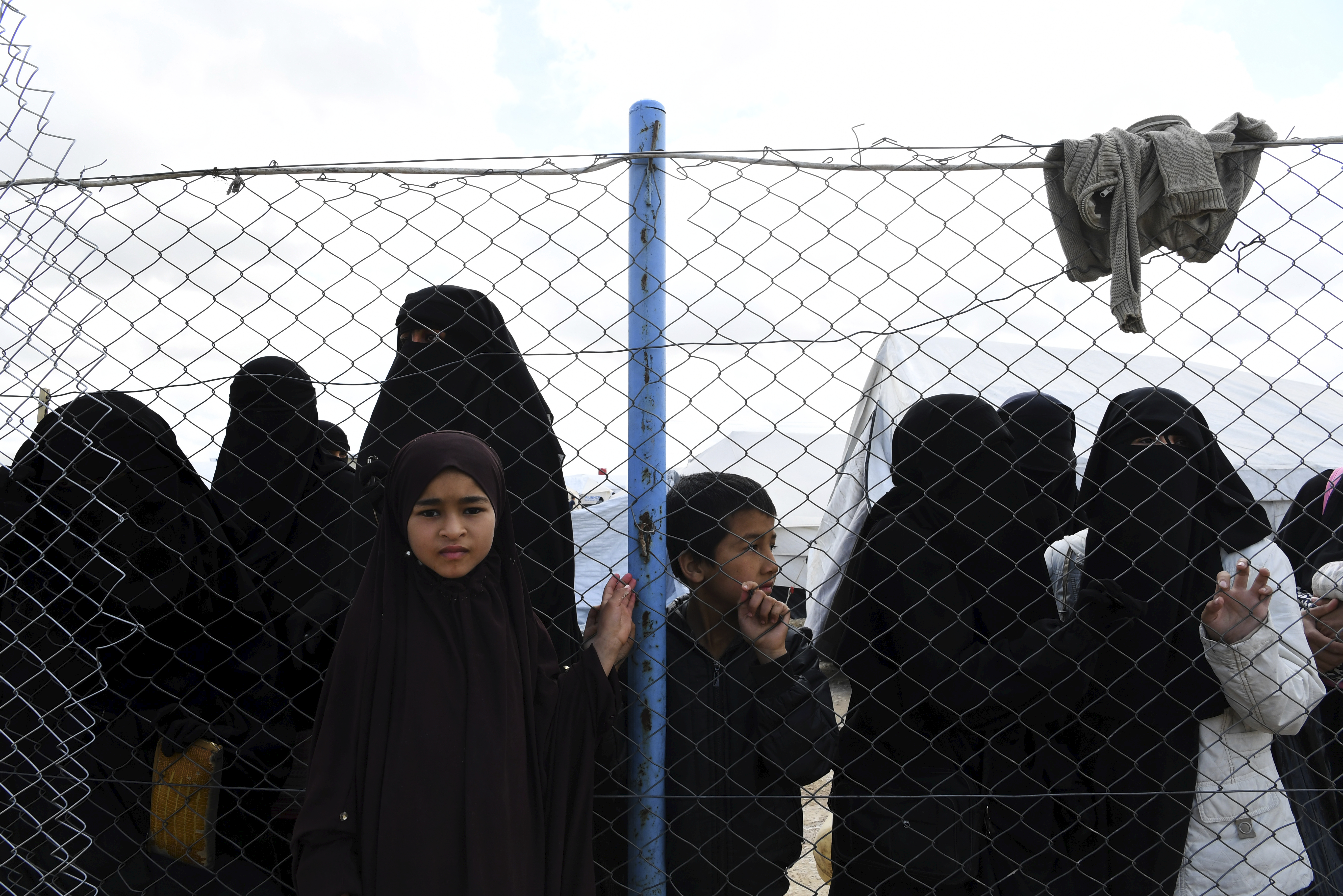Wives and childern of former ISIS fighters gather at the fence in the foreign section of the al-Hawl refugee camp in northern Syria on April 2, 2019. The camp is home to around 72,000 people displaced from territories that were formerly occupied by Islamic State.