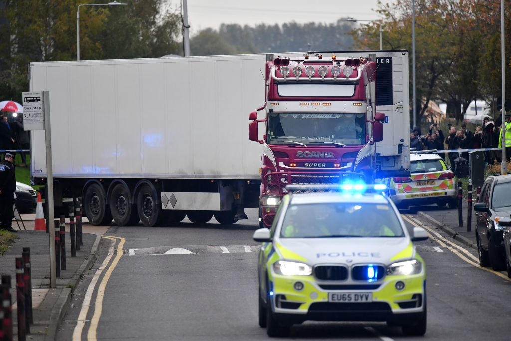 Police officers drive away a truck in which 39 dead bodies were discovered on Oct. 23, in the U.K. The victims are believed to be Vietnamese nationals.