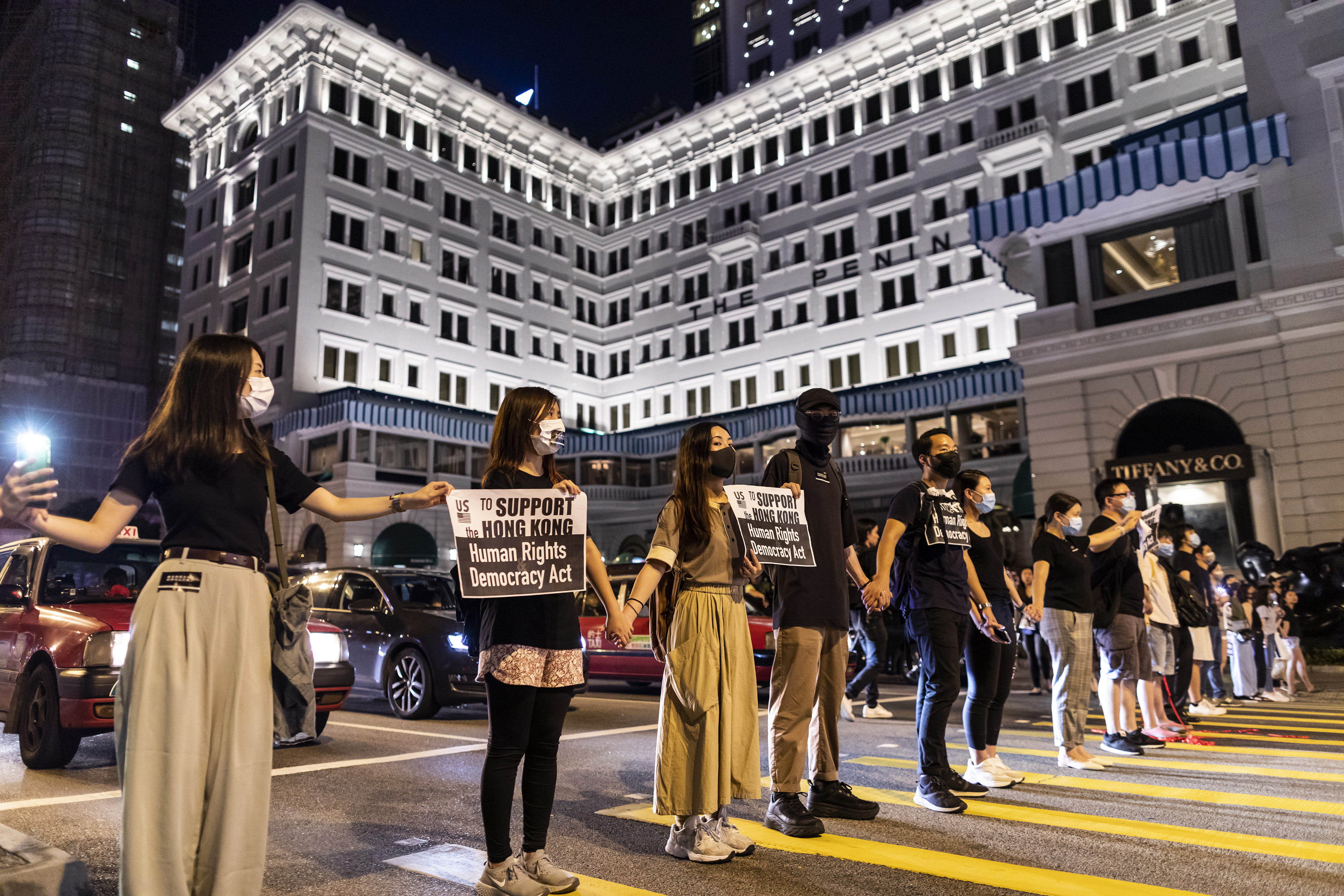 Demonstrators join hands to form a human chain in front of the Peninsula Hotel during the Hong Kong Way event in the Tsim Sha Tsui district of Hong Kong, China, on Friday, Aug. 23, 2019.