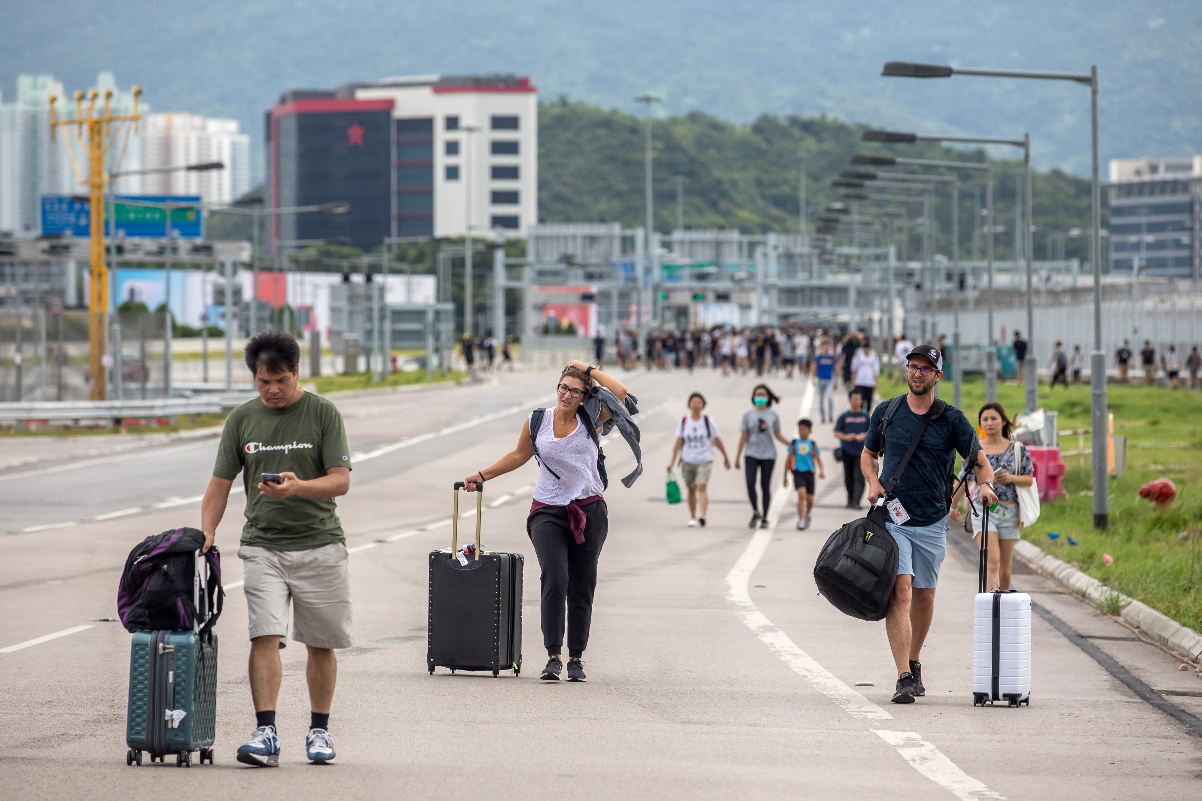 Travelers walk with their luggage along a road towards the Hong Kong International Airport during a protest in Hong Kong, China, on Sunday, Sept. 1, 2019.
