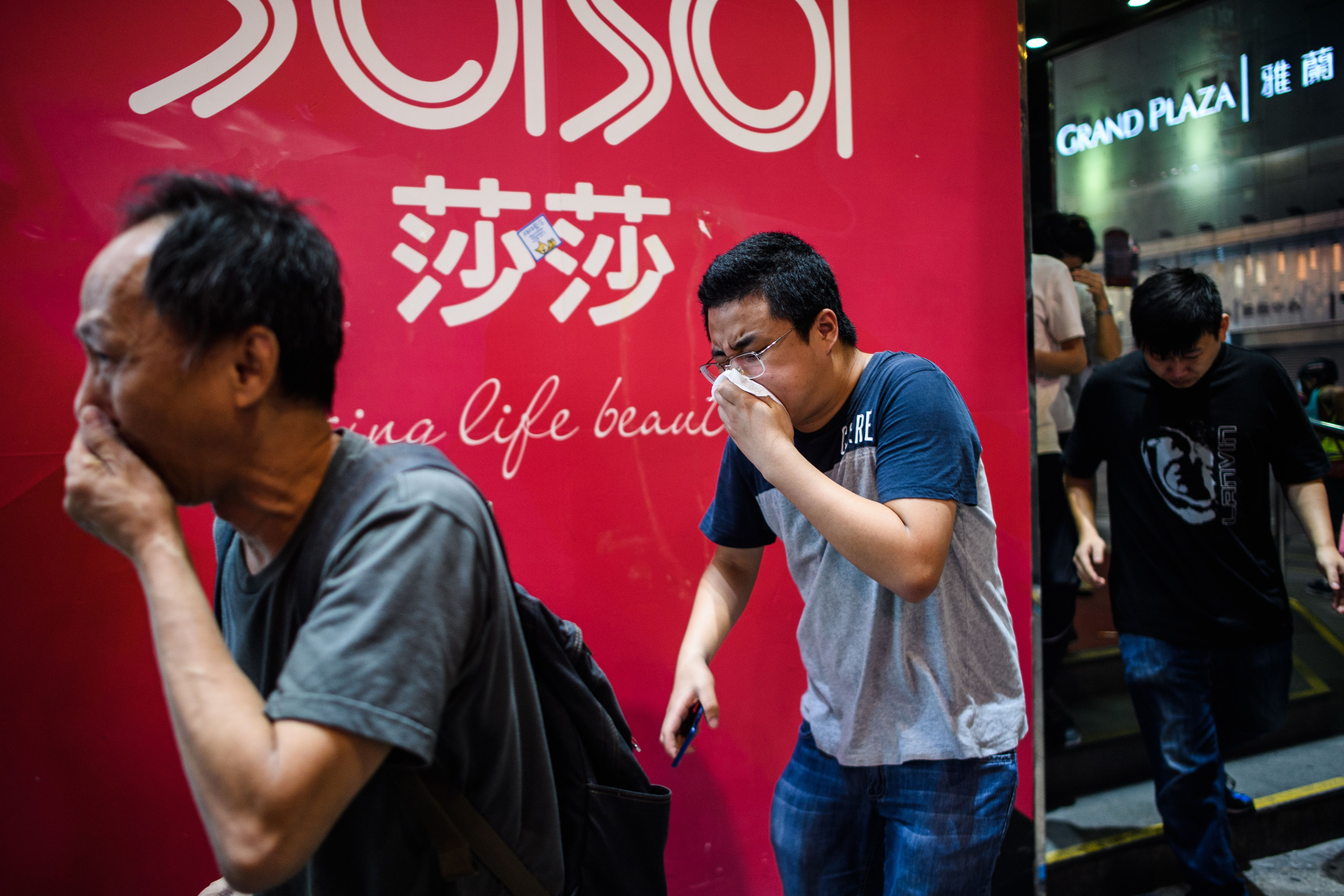 Bystanders react after police fired tear gas to disperse residents and protesters in the Mong Kok district of Kowloon in Hong Kong on October 27, 2019.
