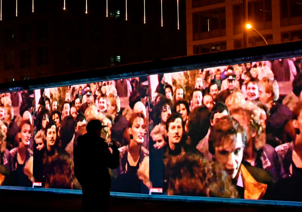 A spectator stands in front of a 3D video installation projected on the so-called East Side Gallery, a 1,3 km-long portion of the Berlin wall, during a rehearsal on November 3, 2019 in Berlin.
