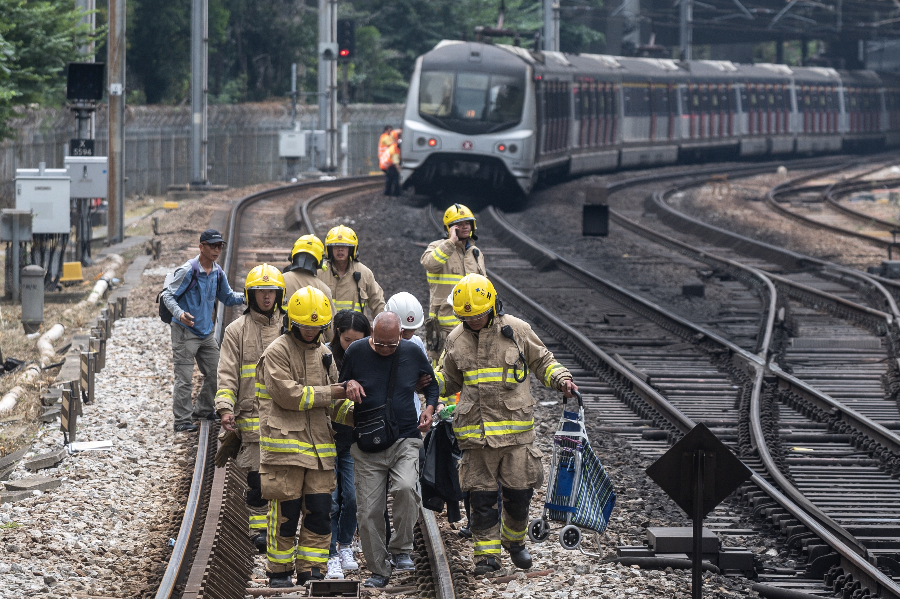 A man is escorted by firemen on the train tracks at Sha Tin MTR station due to the disruption of the train services in Hong Kong on November 12, 2019.