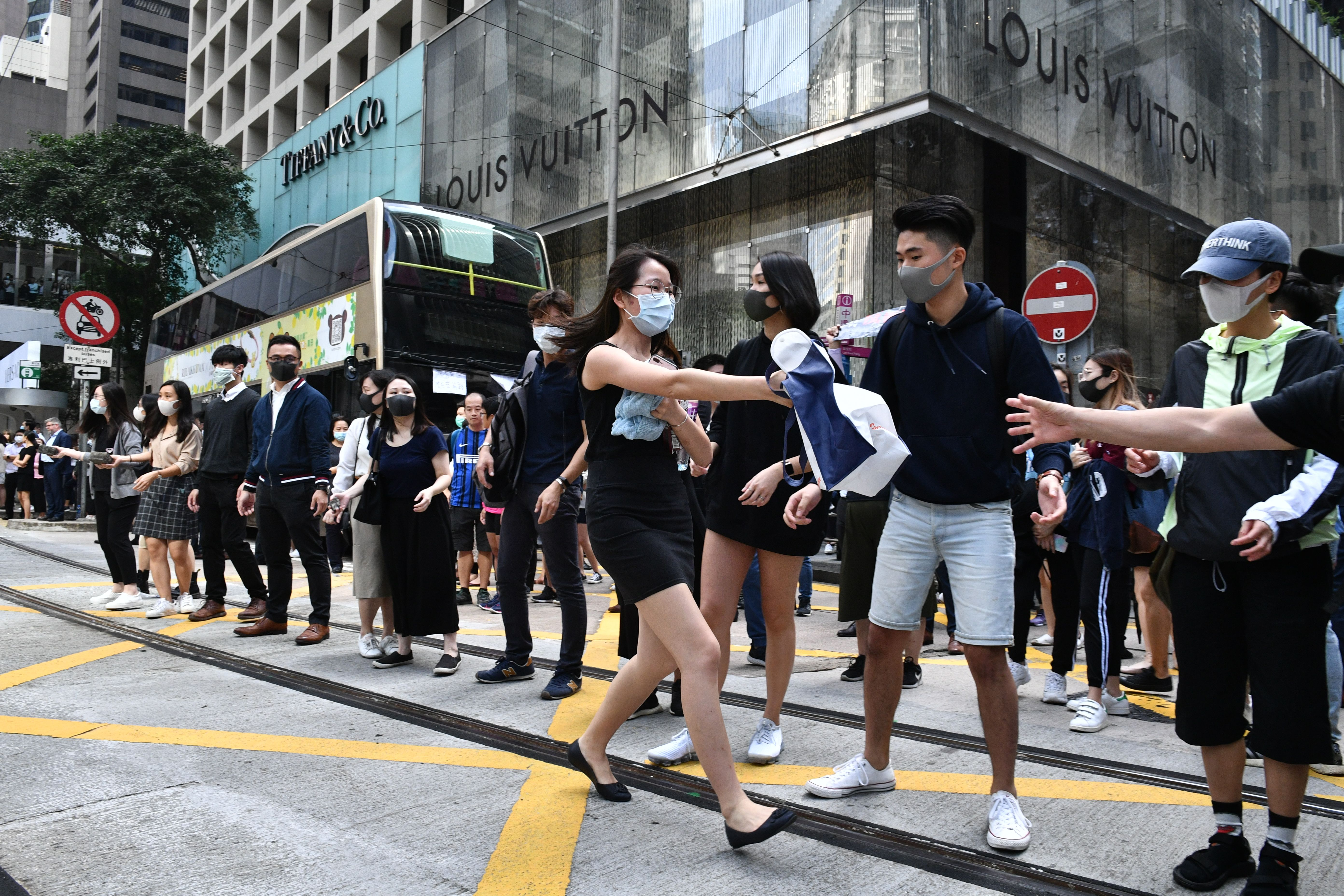 Office workers and pro-democracy protesters form a human chain to pass bricks during a demonstration in Central in Hong Kong on November 12, 2019.