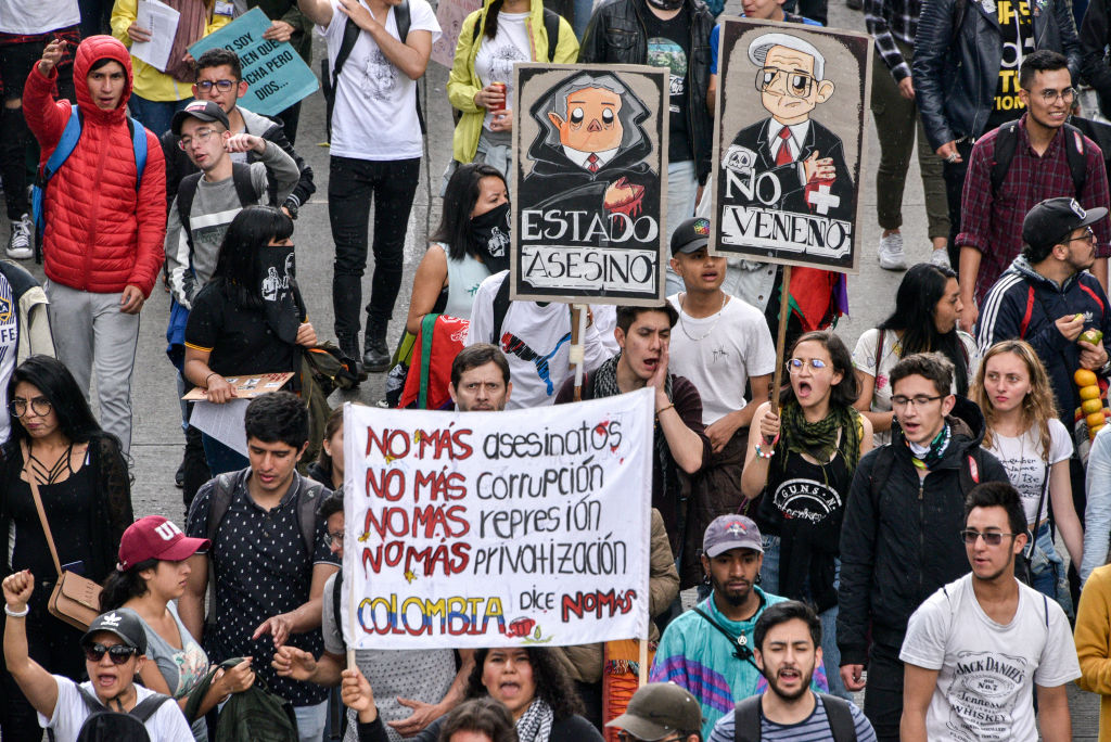 Anti-government demonstrators march holding sign calling for no more assassinations, corruption, repression and privatization Nov. 21, 2019 in Bogota, Colombia.