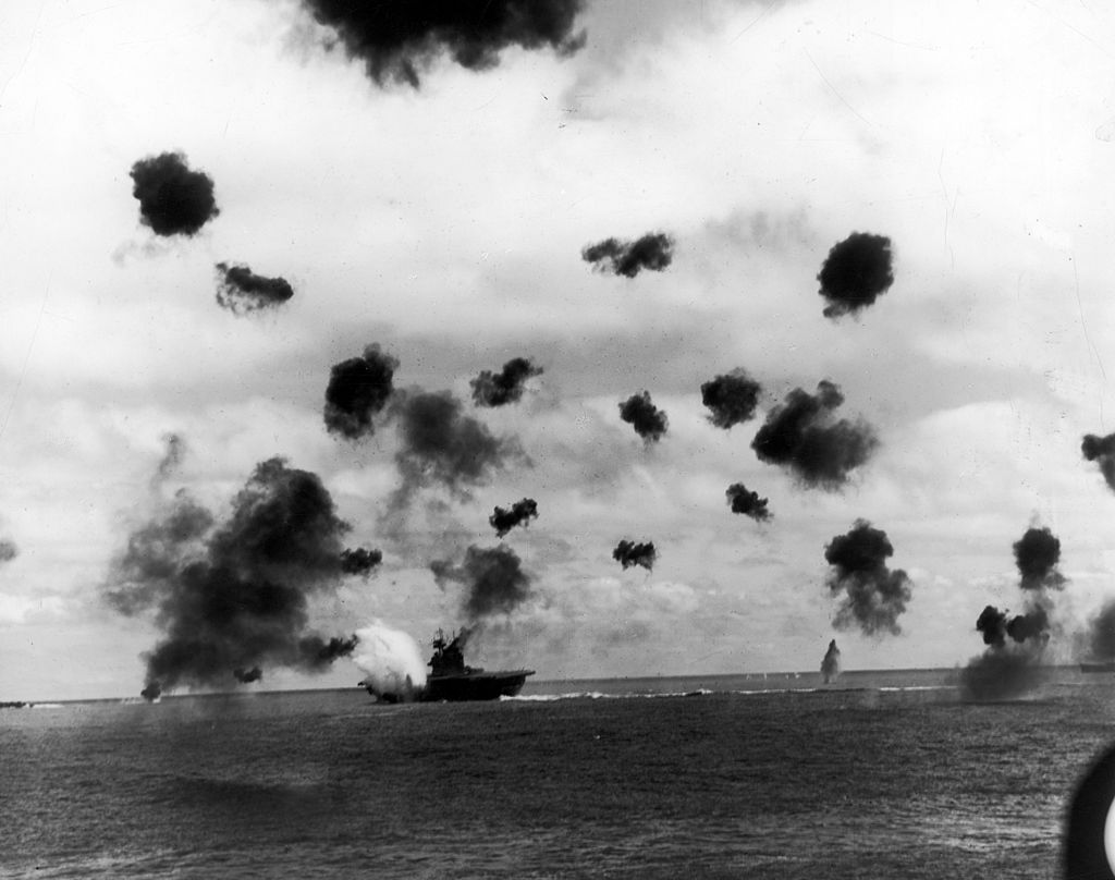 Smoke from antiaircraft guns fills the sky as aircraft carrier USS Yorktown (rear, C) is hit by a Japanese torpedo during the Battle of Midway on June 6, 1942.