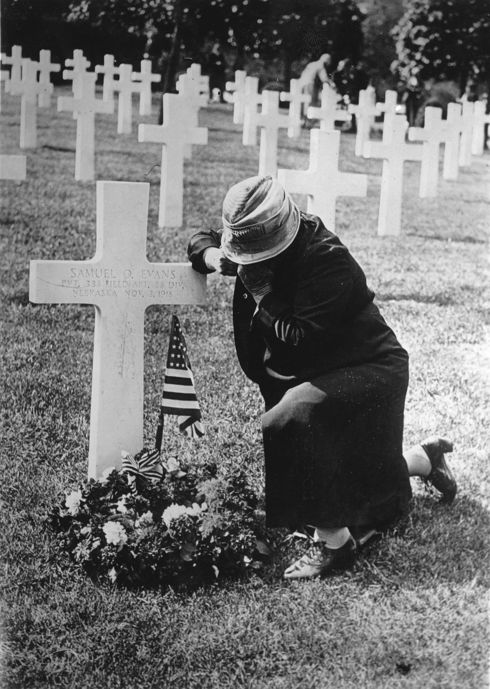 A mother of a soldier at the grave of her son. France, circa 1920