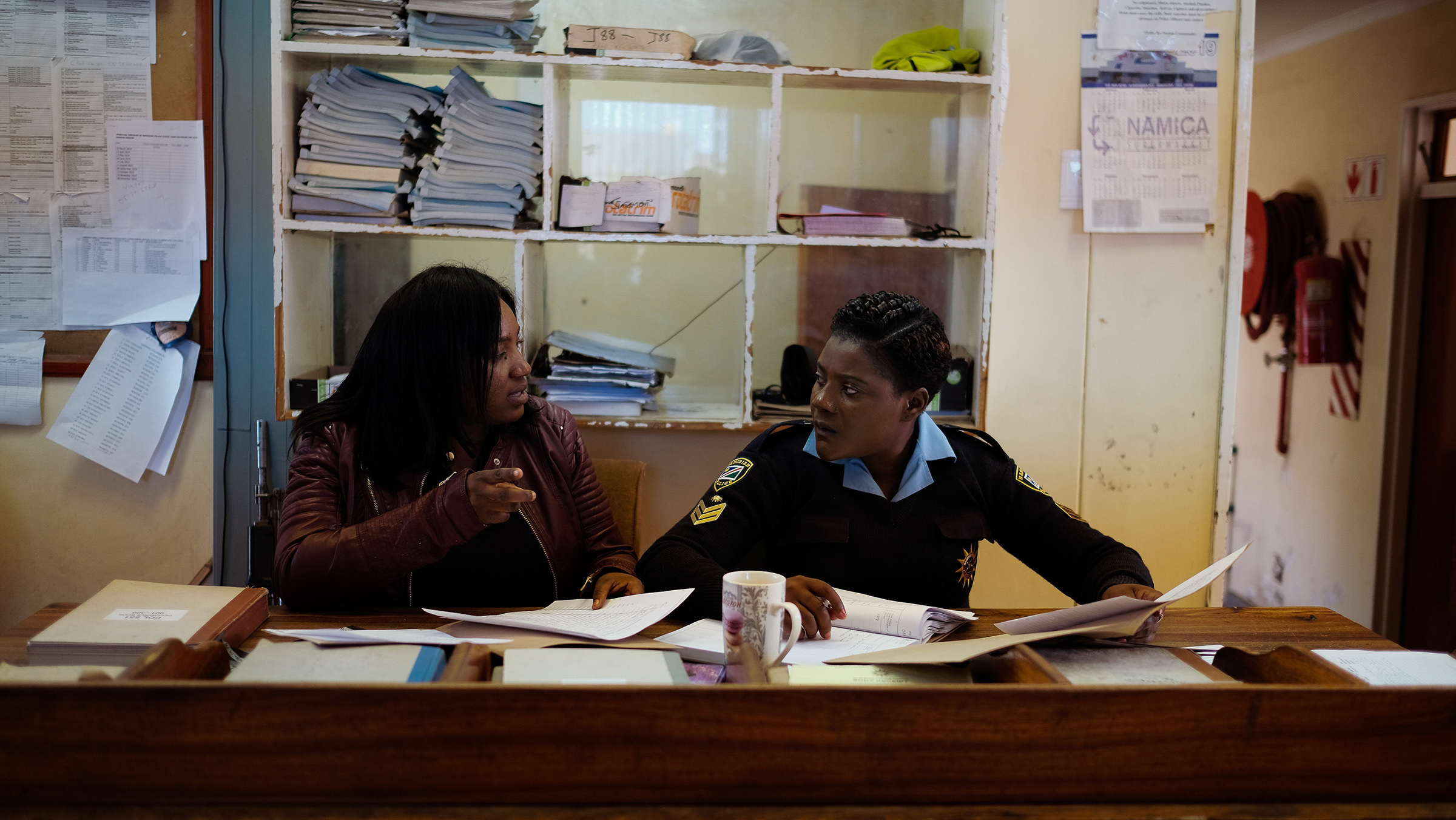 Gender-based Violence Unit Detective Gabriella and Officer Hagatora talk about a possible suspect for a rape case at the Katatura Police Station in Windhoek, Namibia in the summer of 2019.