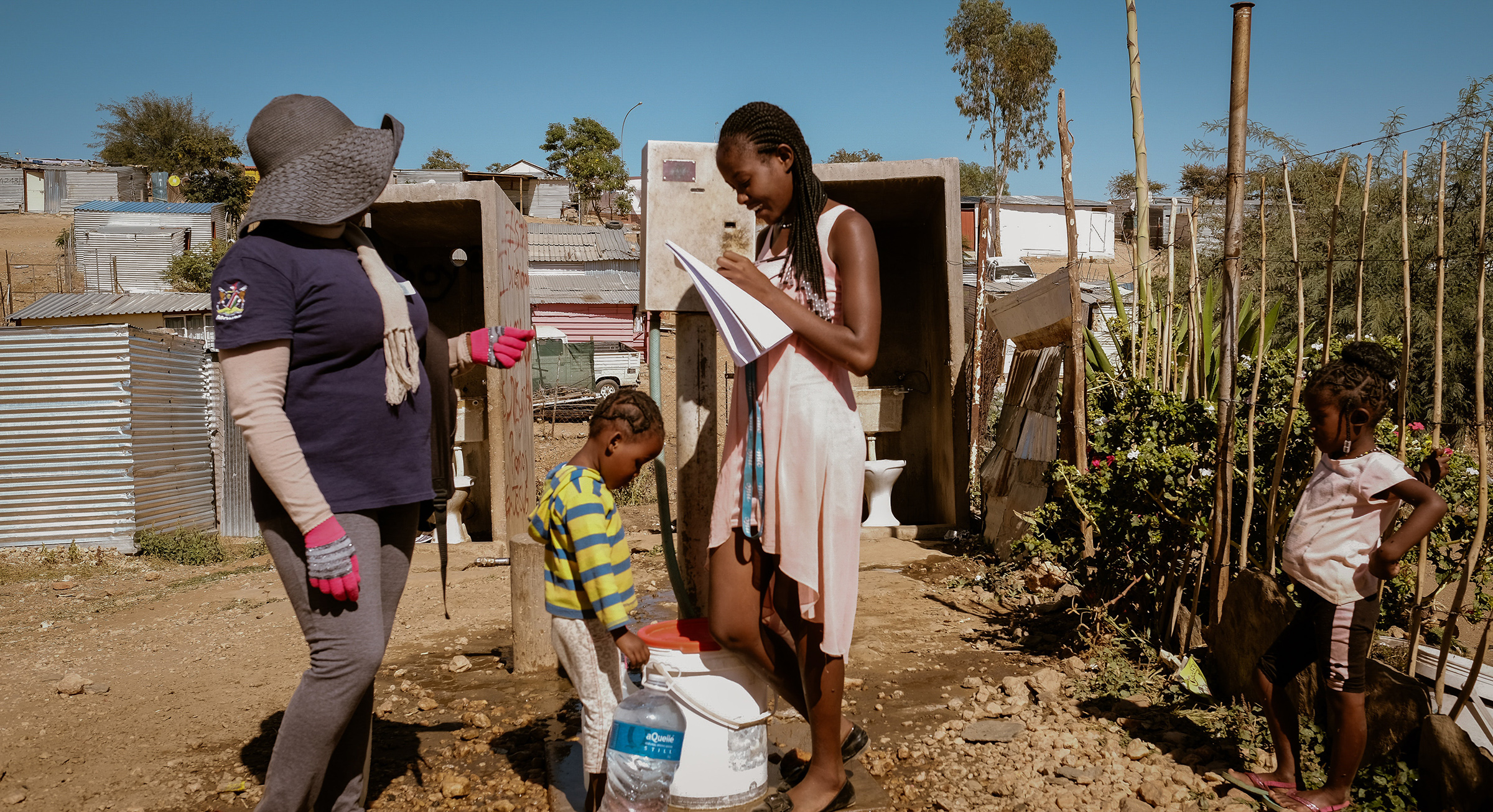 A DREAMS recruiter signs a woman up for the program while getting her daily water from a well in the Katatura unsettled camps in Namibia, in the summer of 2019.