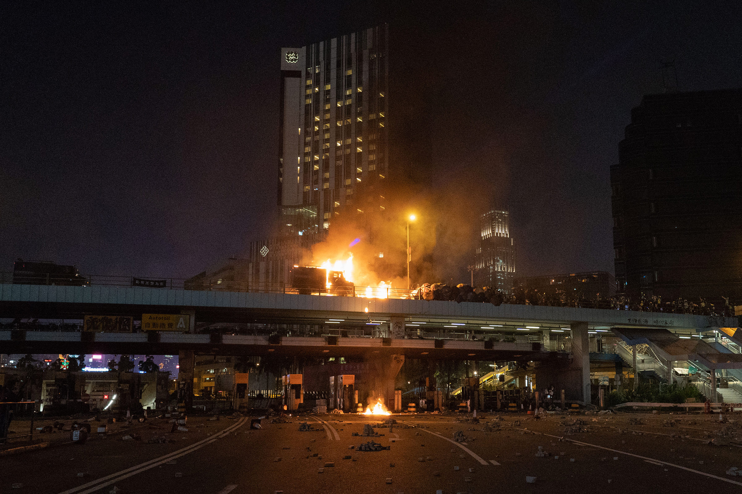 An armored police van is engulfed in flames  on a bridge overlooking the Cross-Harbour Tunnel, Nov. 17, 2019.