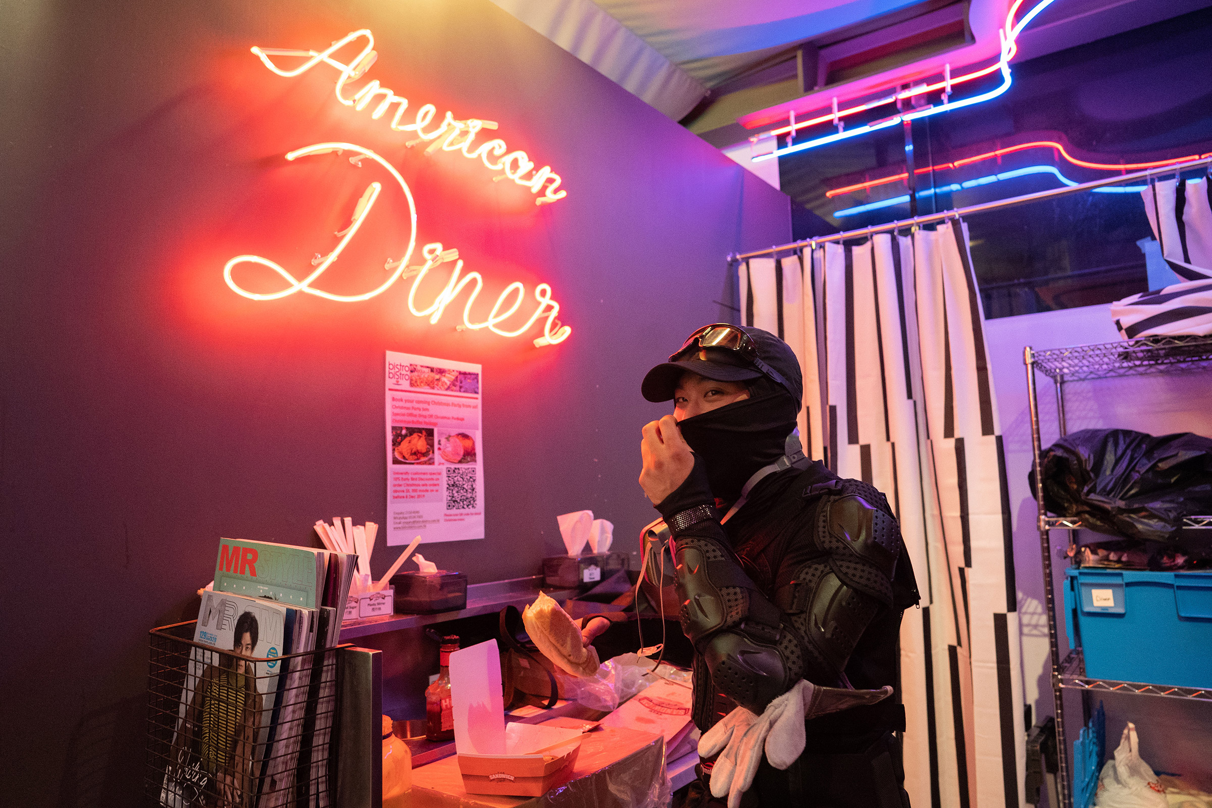 A frontline protestor eats a late-night hot dog at the  American Diner  on the Polytechnic University campus, Nov. 15, 2019.