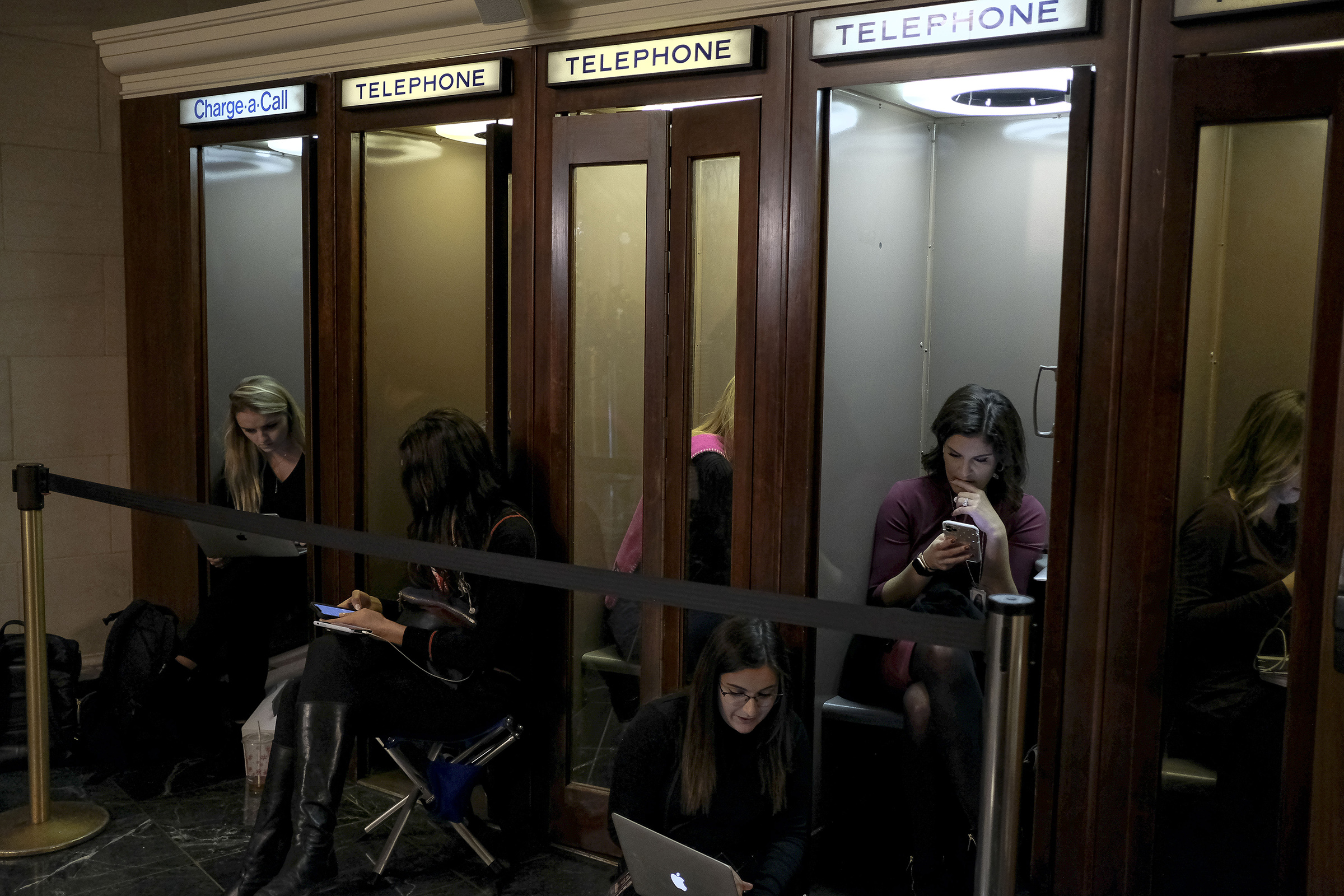 Members of the press sit in phone booths outside the House Intelligence Committee room during the hearing on the impeachment inquiry on Capitol Hill in Washington, D.C. on Nov. 19, 2019.