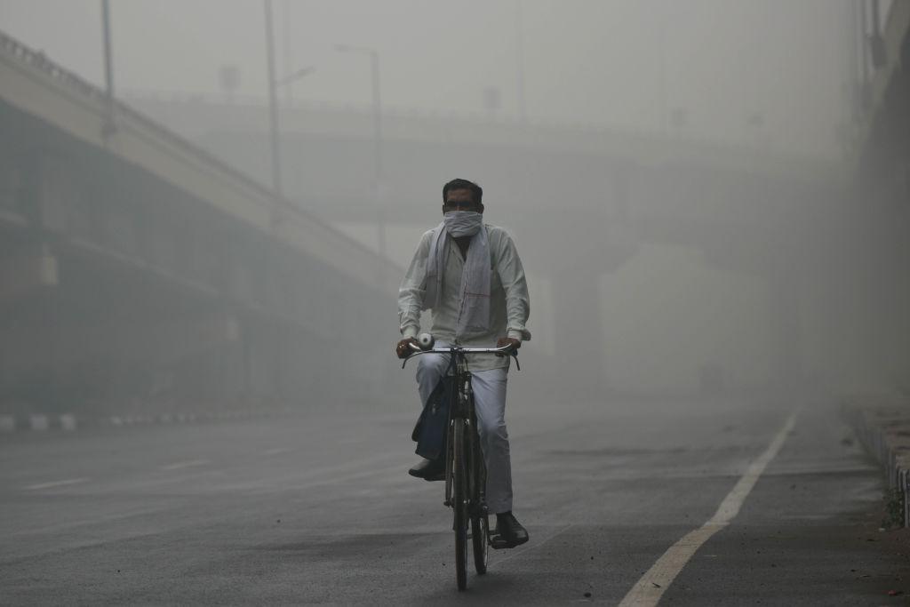 A man rides his bicycle amid dense haze, smoke and low visibility, at Sarai Kale Khan, on Nov. 3, 2019 in New Delhi, India.