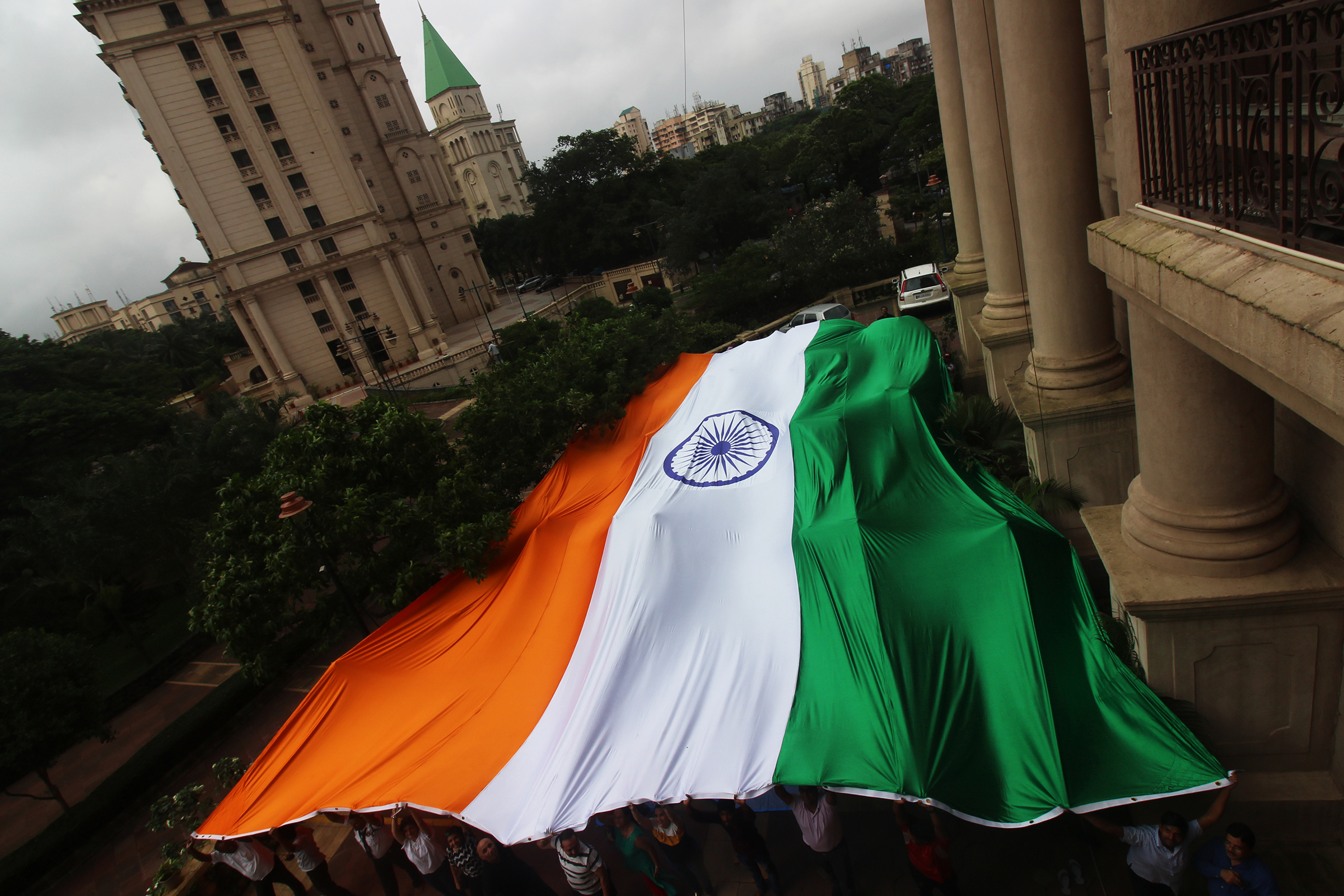 People hold a giant Indian national flag ahead of the 73rd Independence Day celebrations in Mumbai in August 2019.