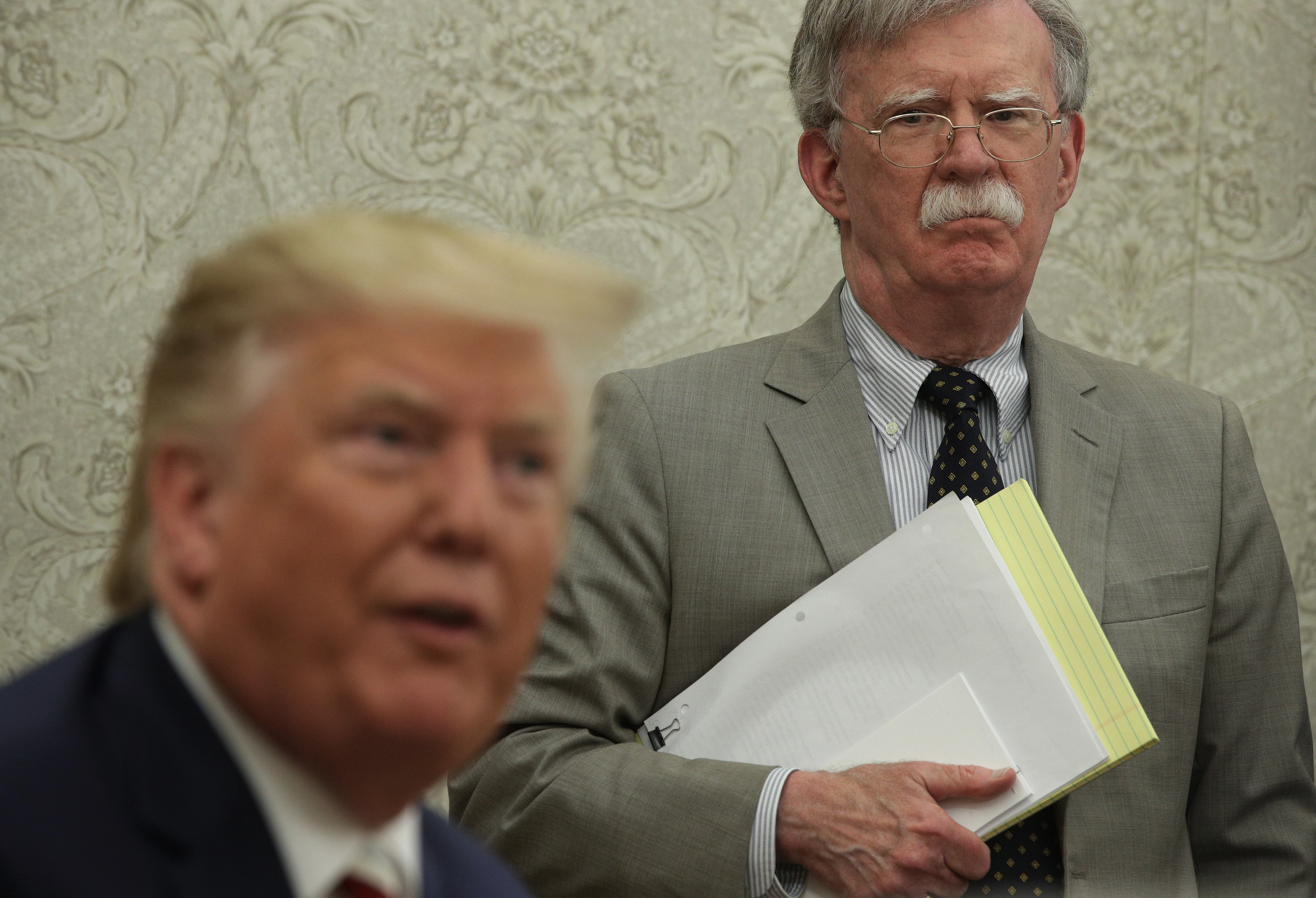 President Donald Trump speaks to members of the media as National Security Adviser John Bolton listens during a meeting with President of Romania Klaus Iohannis in the Oval Office of the White House on Aug. 20, 2019 in Washington, D.C.