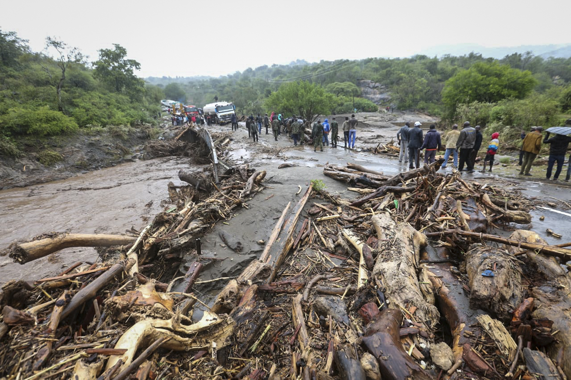 Passengers from stranded vehicles stand next to the debris from floodwaters, on the road from Kapenguria, in West Pokot county, in western Kenya Saturday, Nov. 23, 2019.
