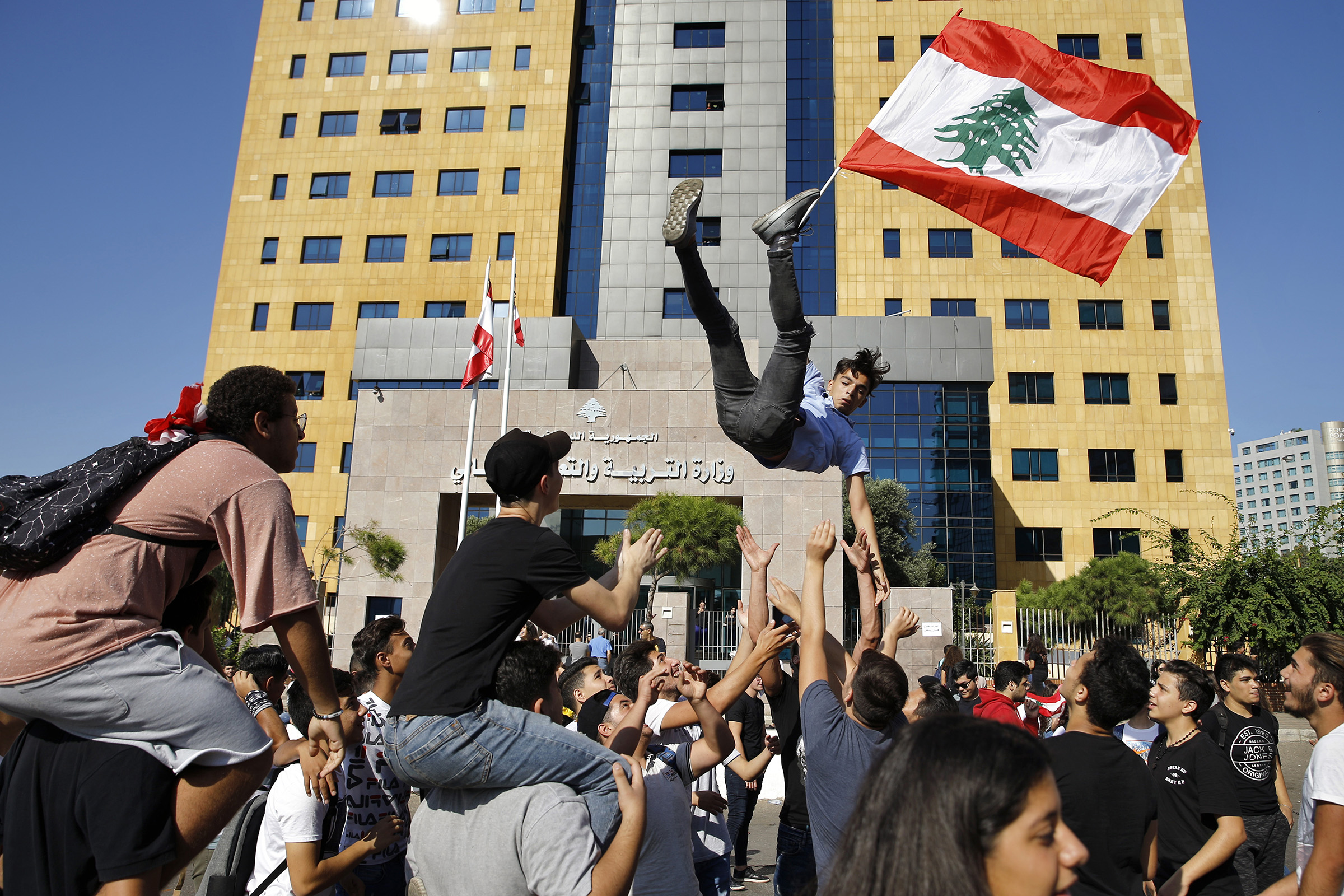 A student protester is thrown into the air by his colleagues as he holds a Lebanese flag during ongoing protests against the Lebanese government, in front of the education ministry in Beirut, Lebanon, on Nov. 12, 2019.