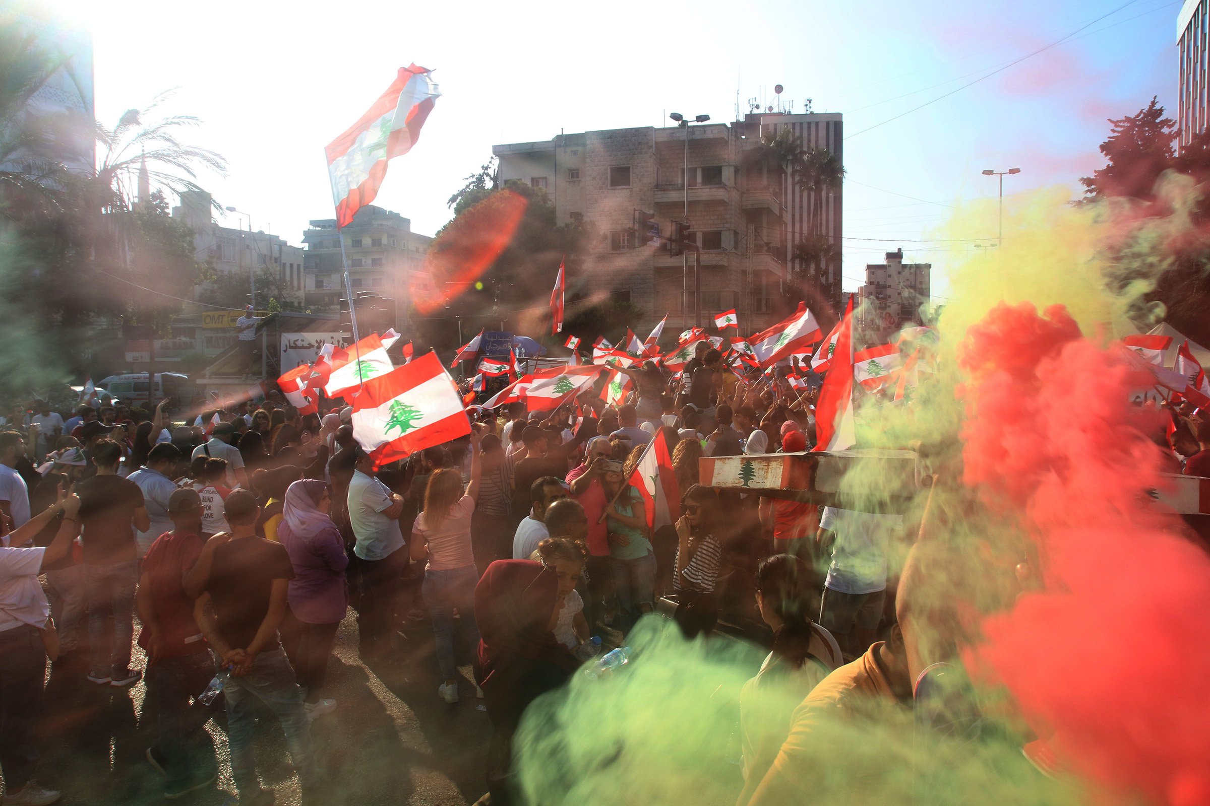 Lebanese protesters wave national flags as they gather in the southern city of Sidon (Saida) on Oct. 19, 2019 for a third day of protests.