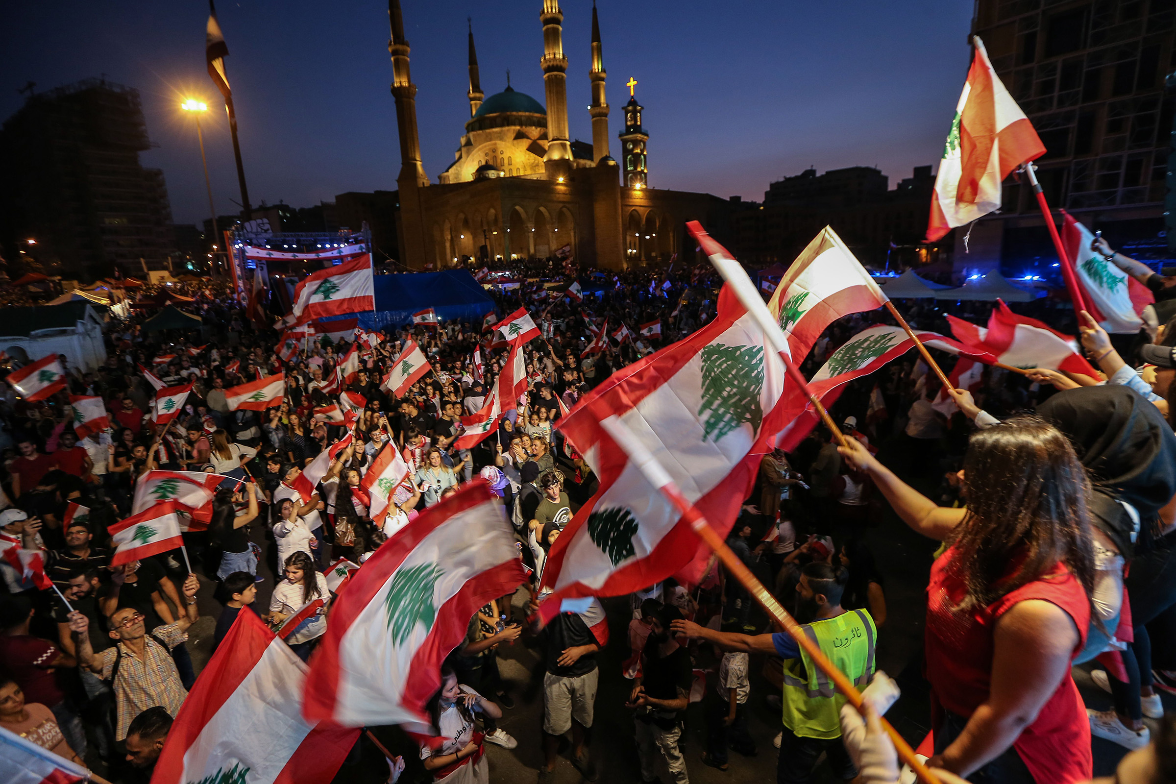 Protesters carry placards, wave Lebanese flags, and shout anti-government slogans during a protest in Martyrs' Square in downtown Beirut, Lebanon, on Oct.27, 2019.