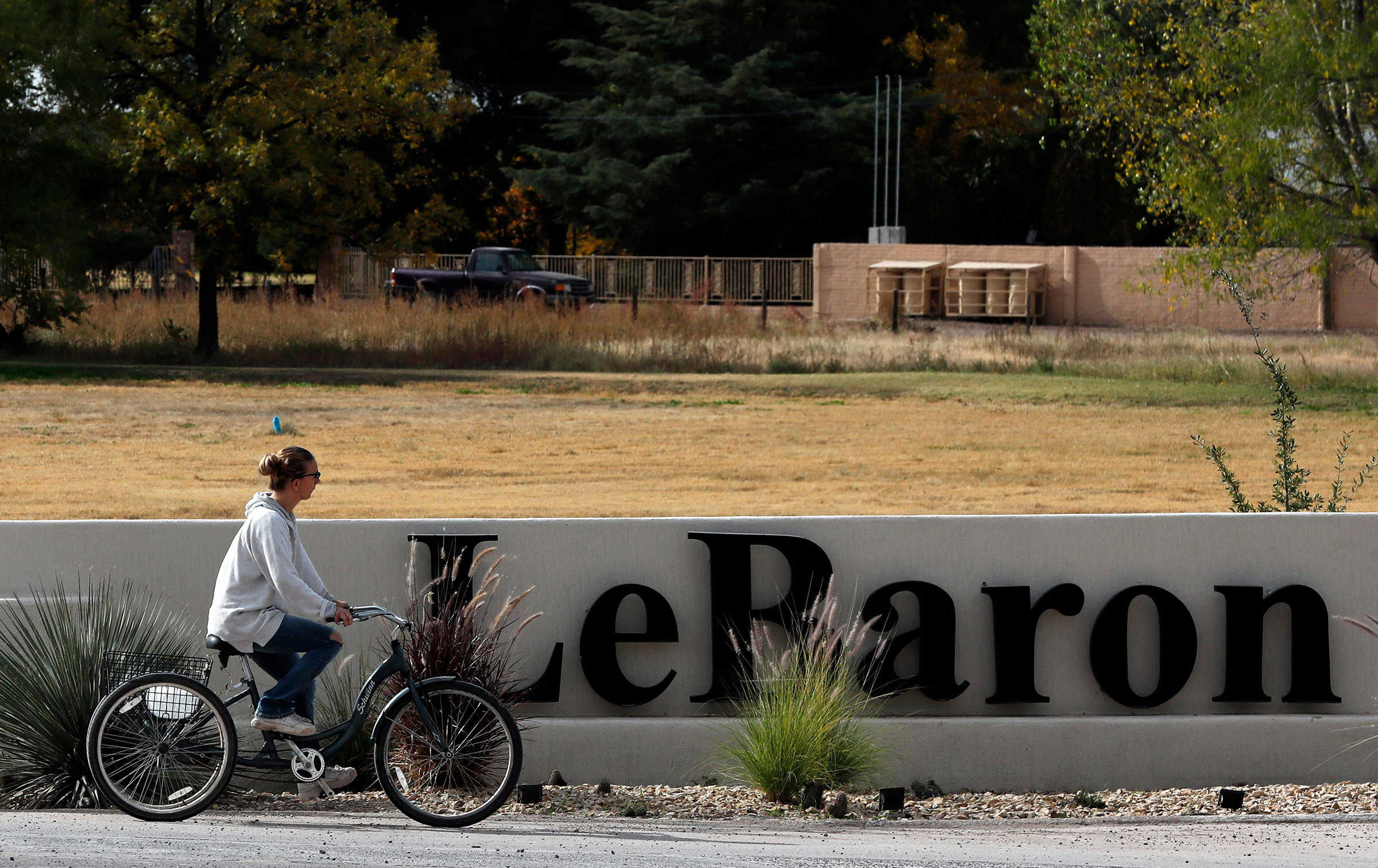 A woman cycles past a sign announcing the Colonia LeBaron, a community settled by members of the extended LeBaron family in Chihuahua state in northern Mexico, Nov. 6, 2019.