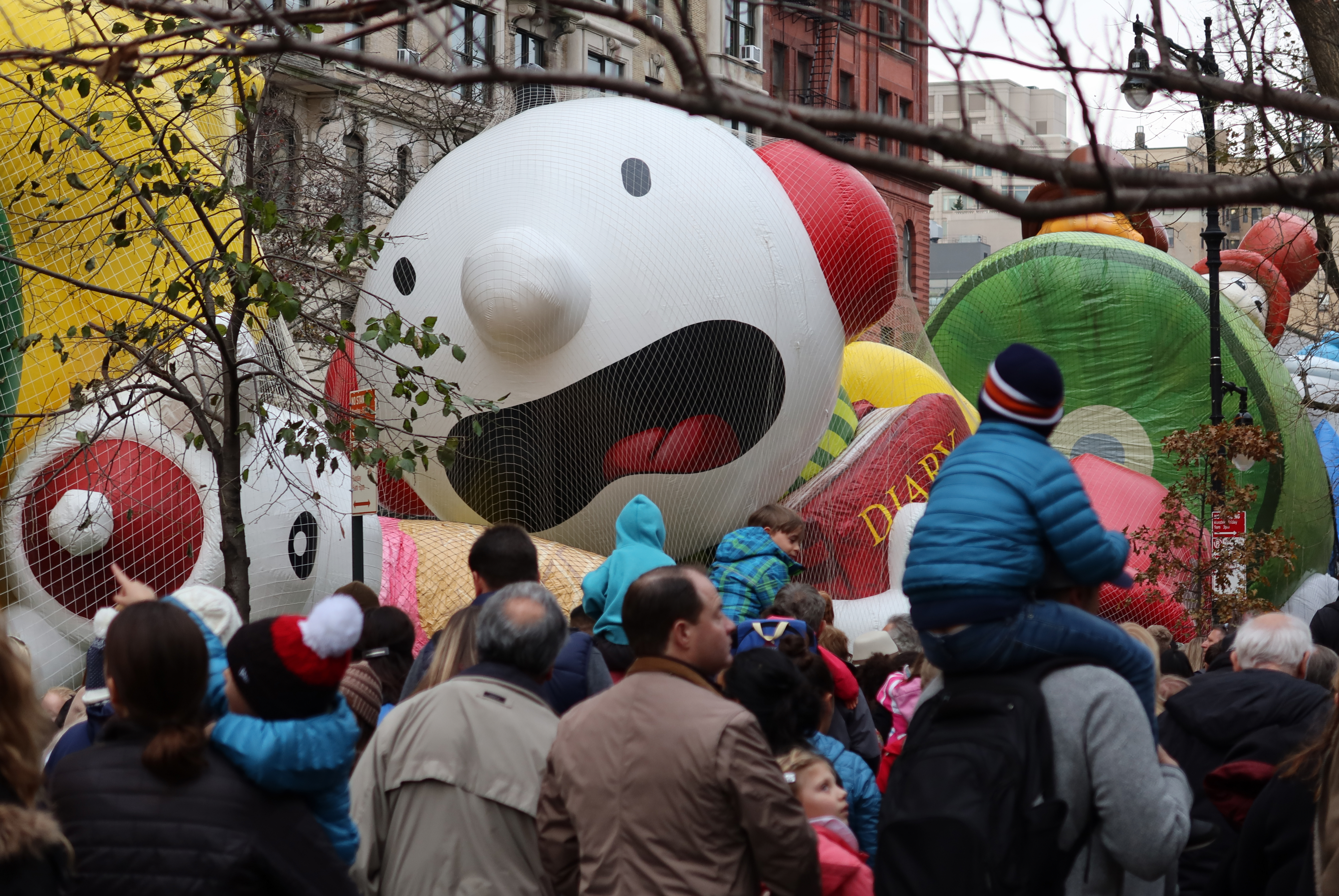 People walk past a  Diary of a Wimpy Kid  balloon after it was inflated for the annual Macy's Thanksgiving Day Parade on Nov/ 27, 2019 in New York City.